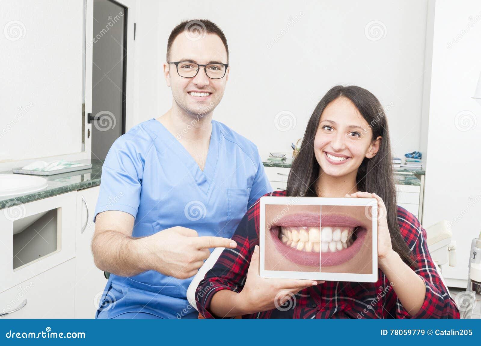 Orthodontist en patiënt die bij tablet en het glimlachen richten