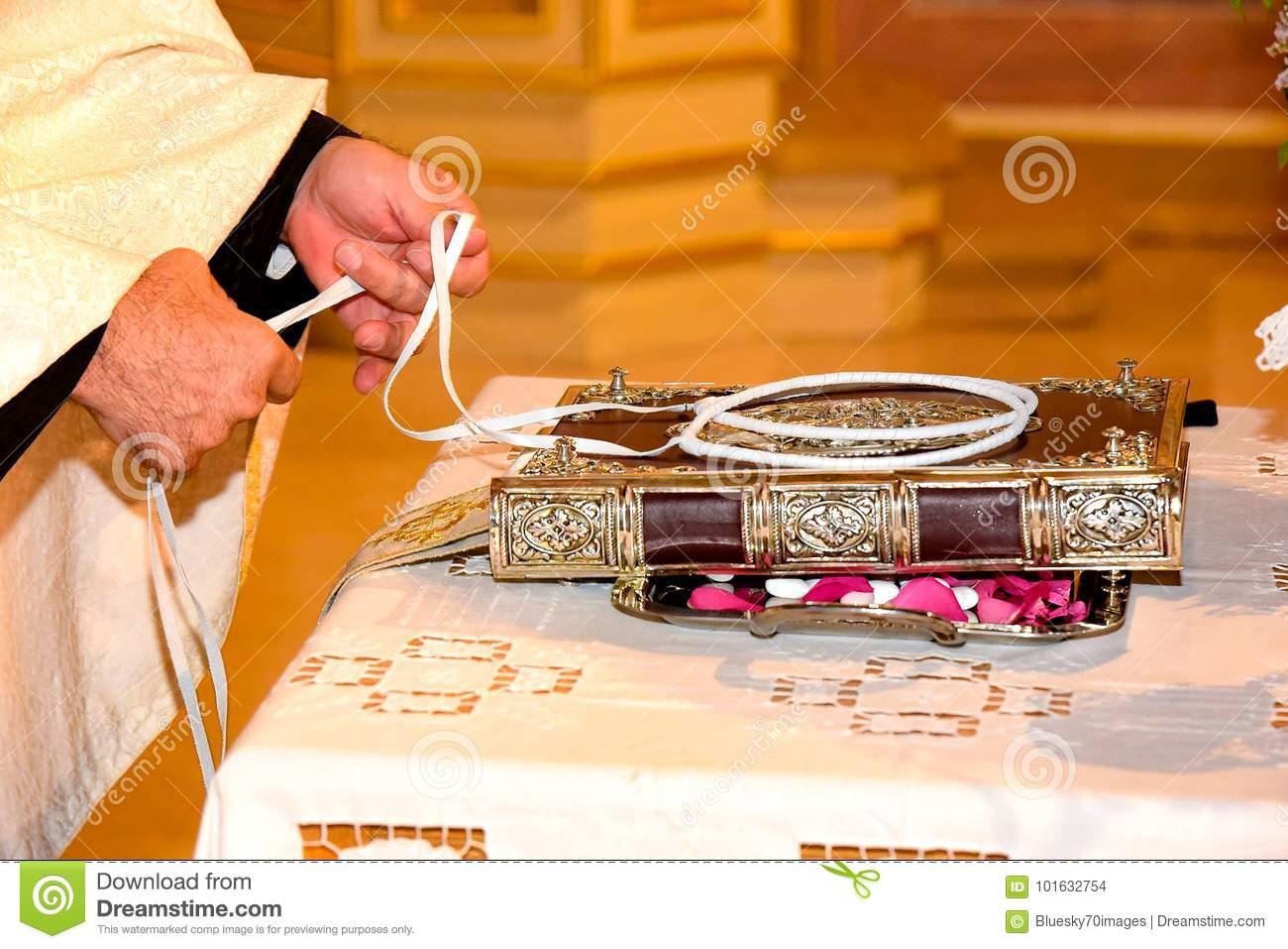 Orthodox Cristian priest hands and wedding crowns decorated on a