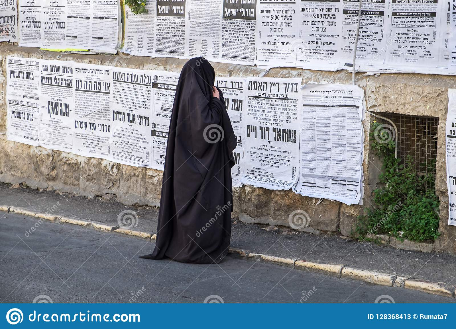 Orthodox jewish `Taliban women` read street poster in jewish quarter