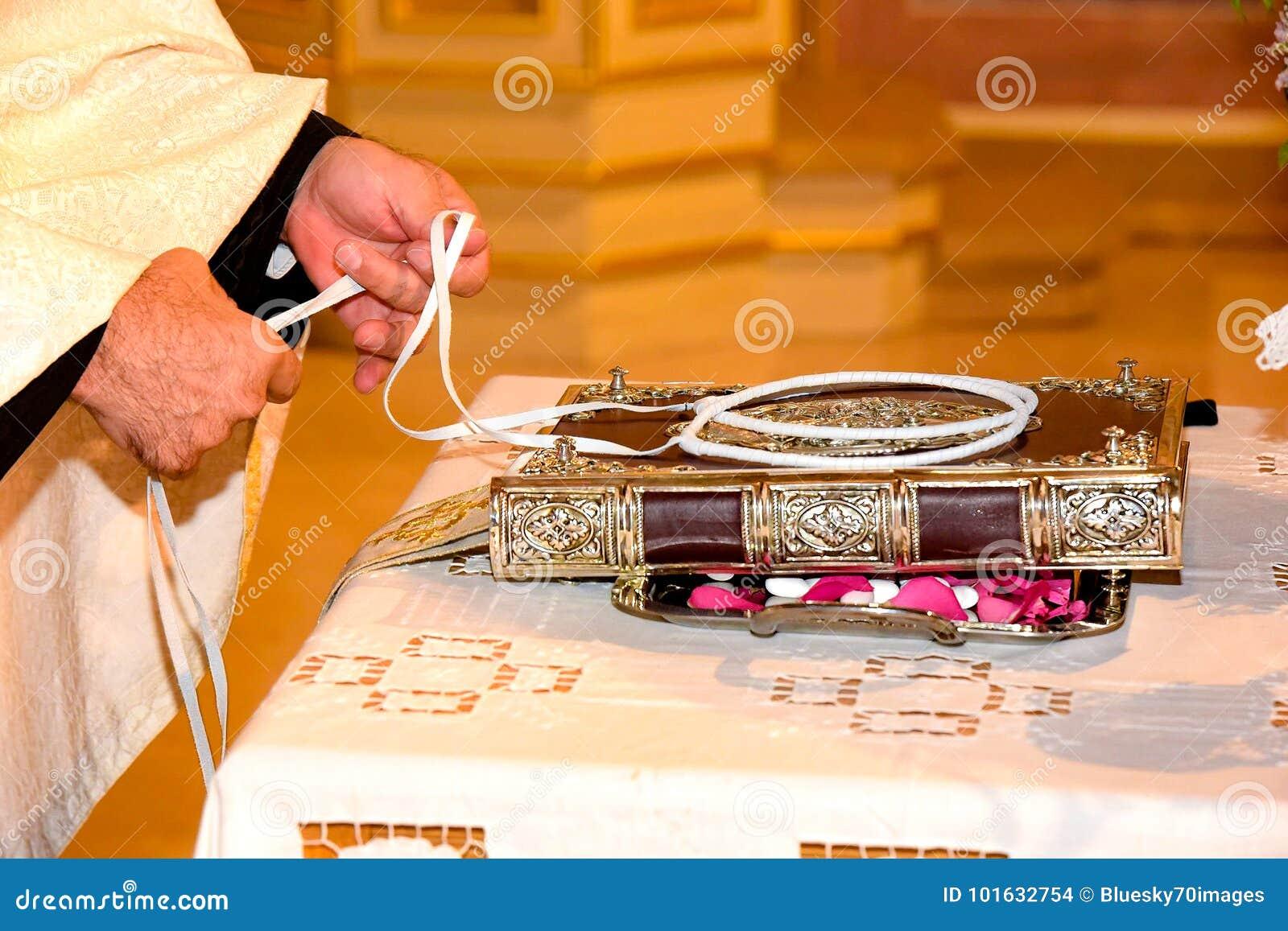 Orthodoxe die de priesterhanden van Cristian en huwelijkskronen op a worden verfraaid