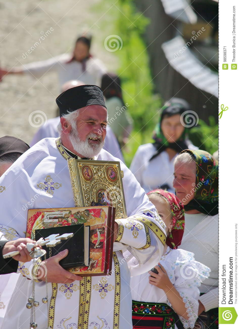 Orthodoxe priester en mensen in traditionele nationale kostuums - een dorp in Maramures, Roemenië