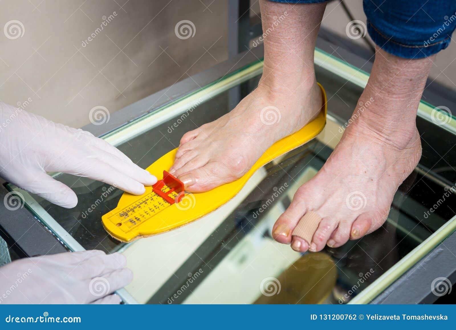 Ortopedi och medicin Ung Caucasian form för mätning för format för handskar för latex för tatuering för doktorshandman av foten f