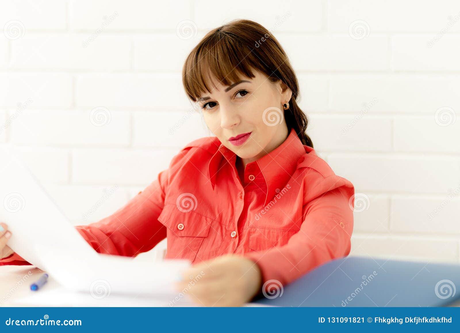 Ortrait av den unga lyckliga le affärskvinnan som arbetar med dokument på kontoret
