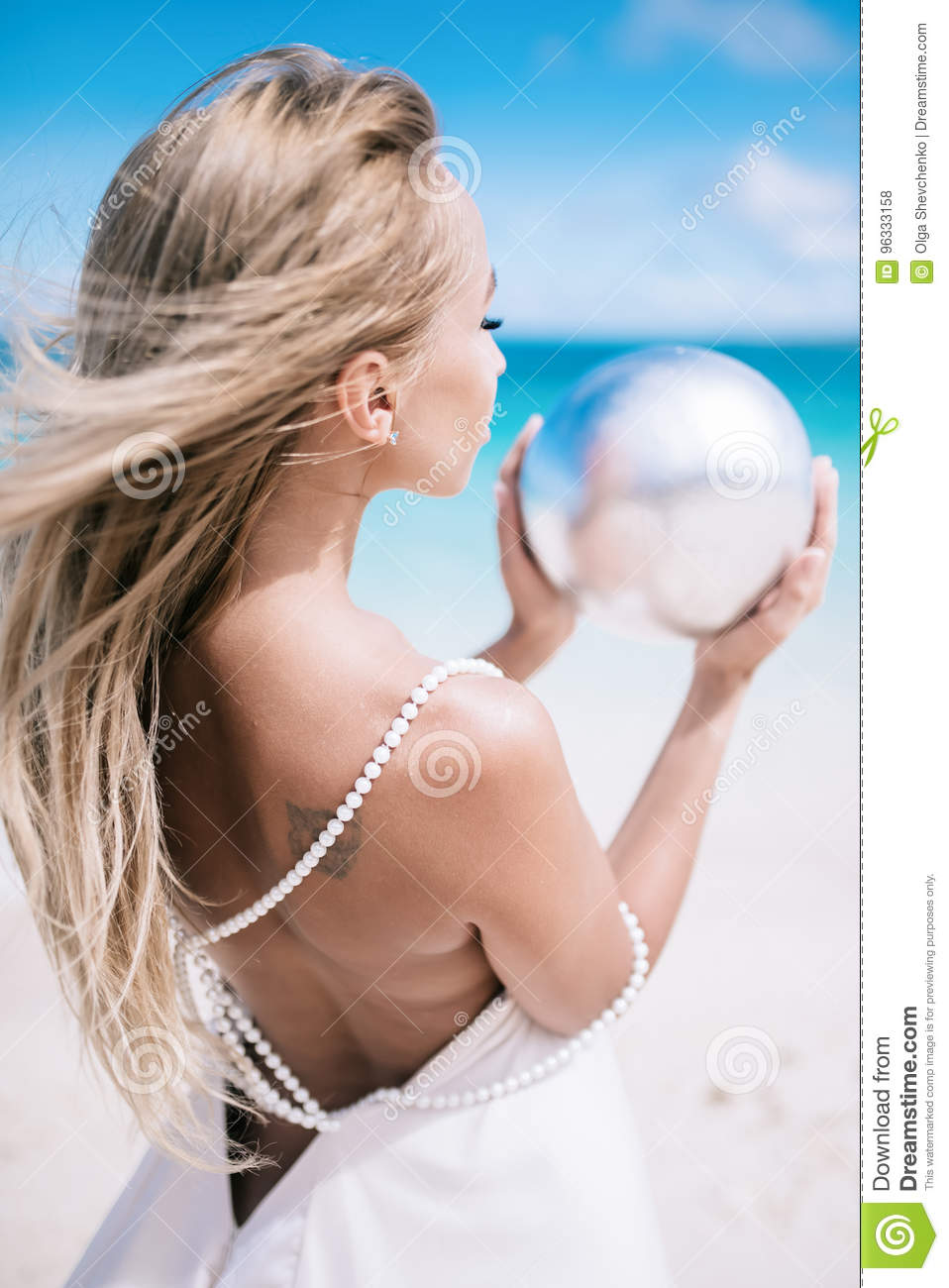 Ortrait of the beautiful blond long hair bride in a open back wedding dress stand on the white sand beach with a pearl.