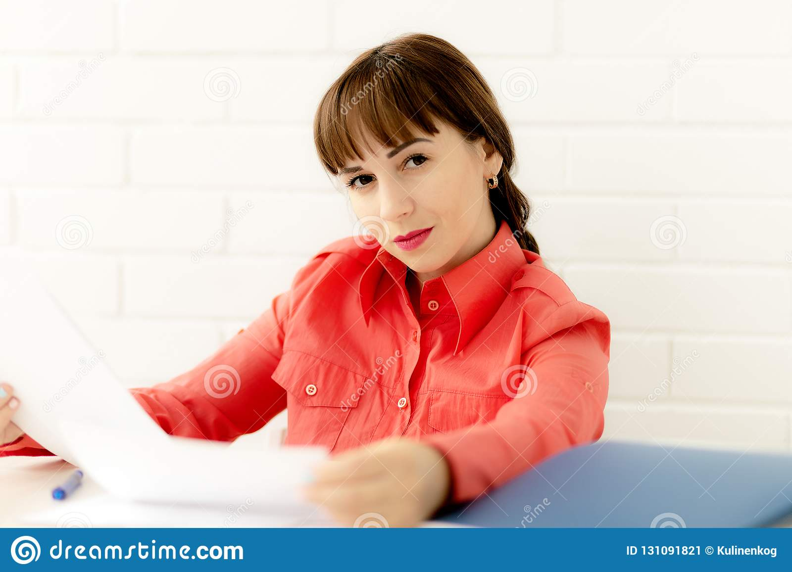 Ortrait of young happy smiling business woman working with documents at office
