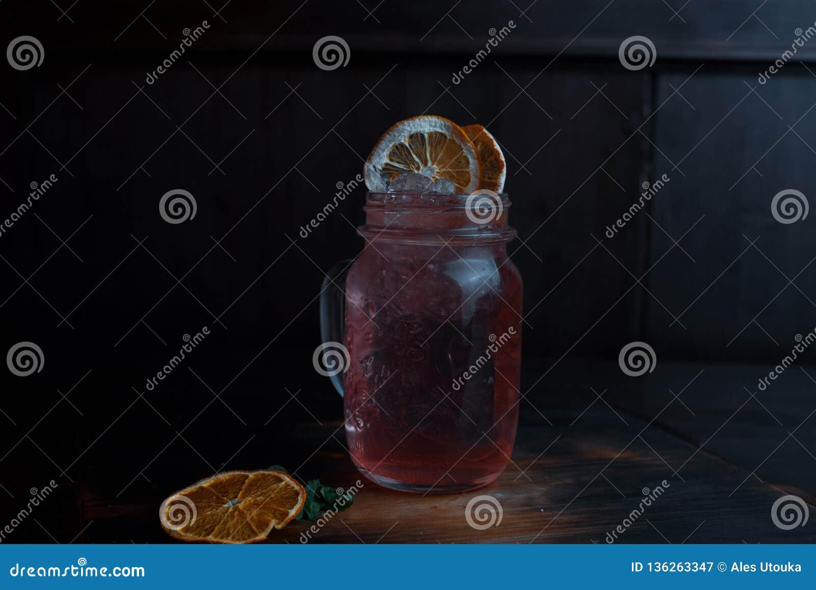 Oryginalny alkoholiczek menchii koktajl z tequila i ajerówka z malinowym syropem, dekorującym z wysuszonymi i świeżymi pomarańczo