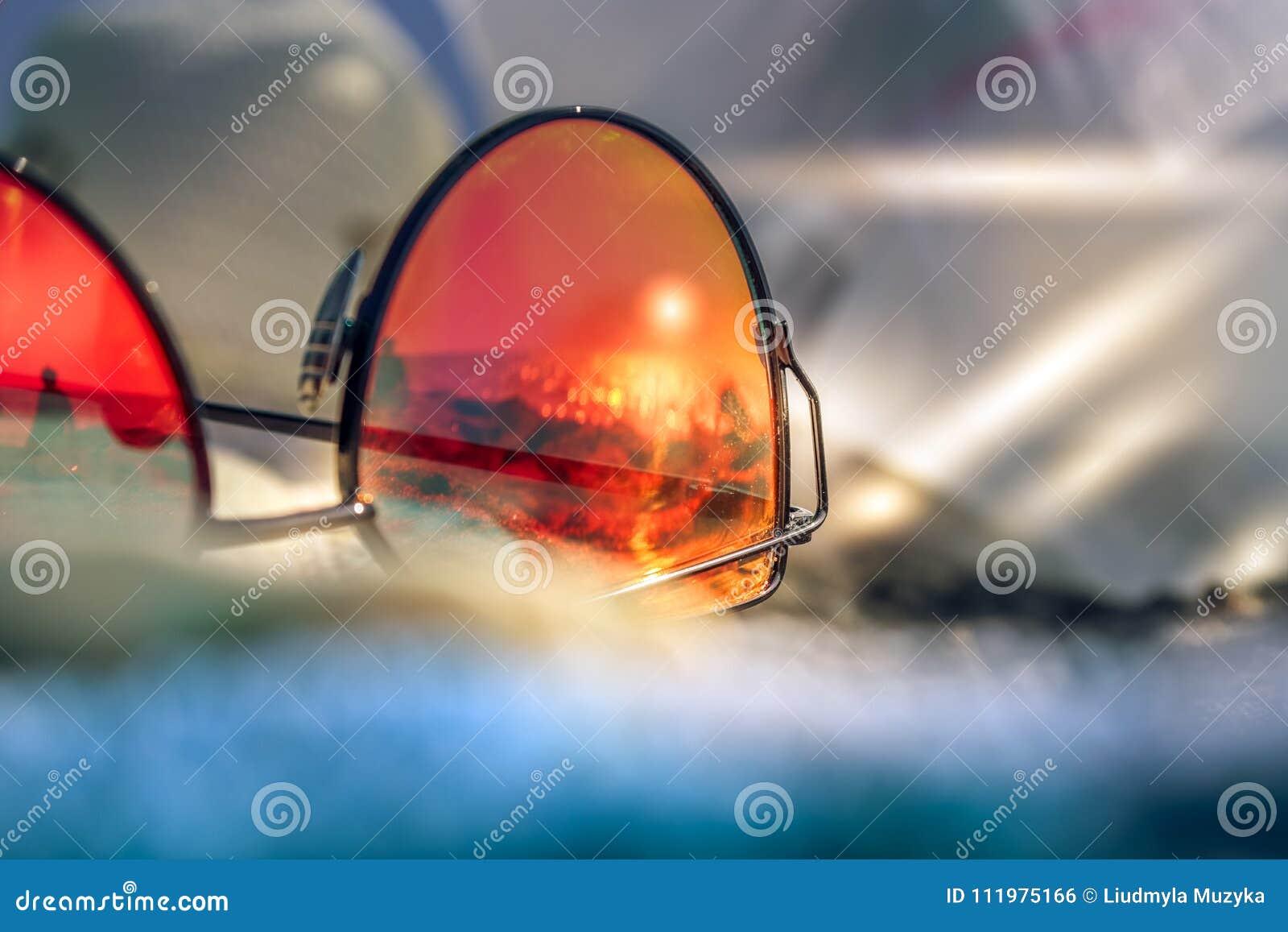 Os óculos de sol com reflexão do verão encalham com areia, o sol e o mar pretos Capri Italy