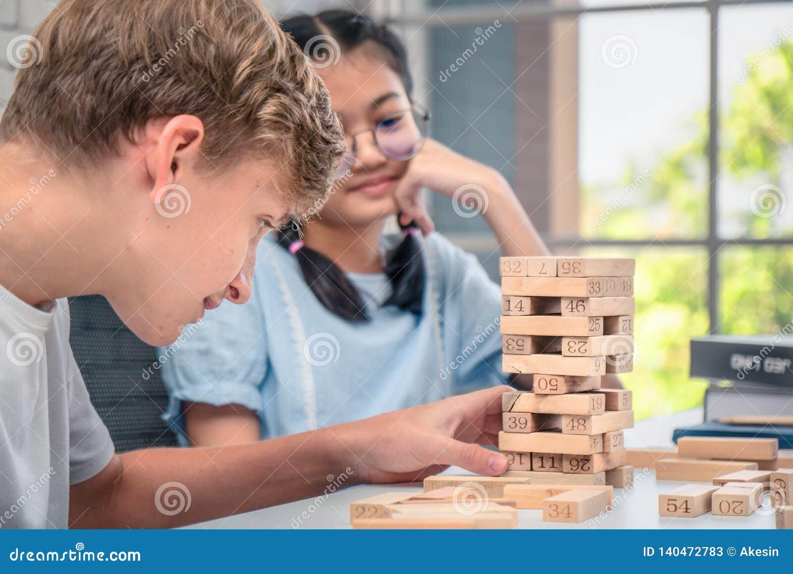 Os adolescentes jogam o jogo de Jenga junto