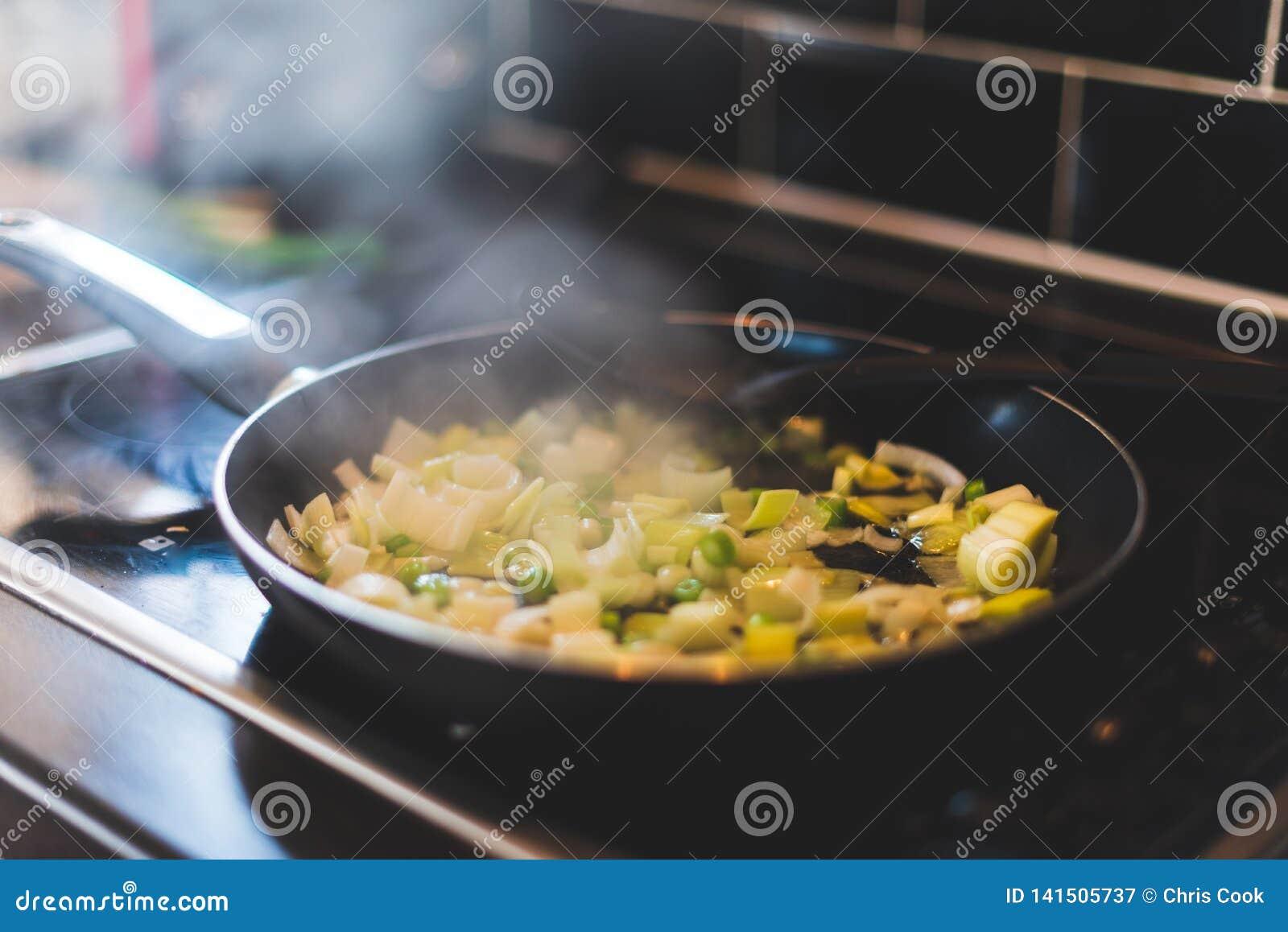 Os alho-porros e outros vegetais estão sendo cozinhados em uma frigideira