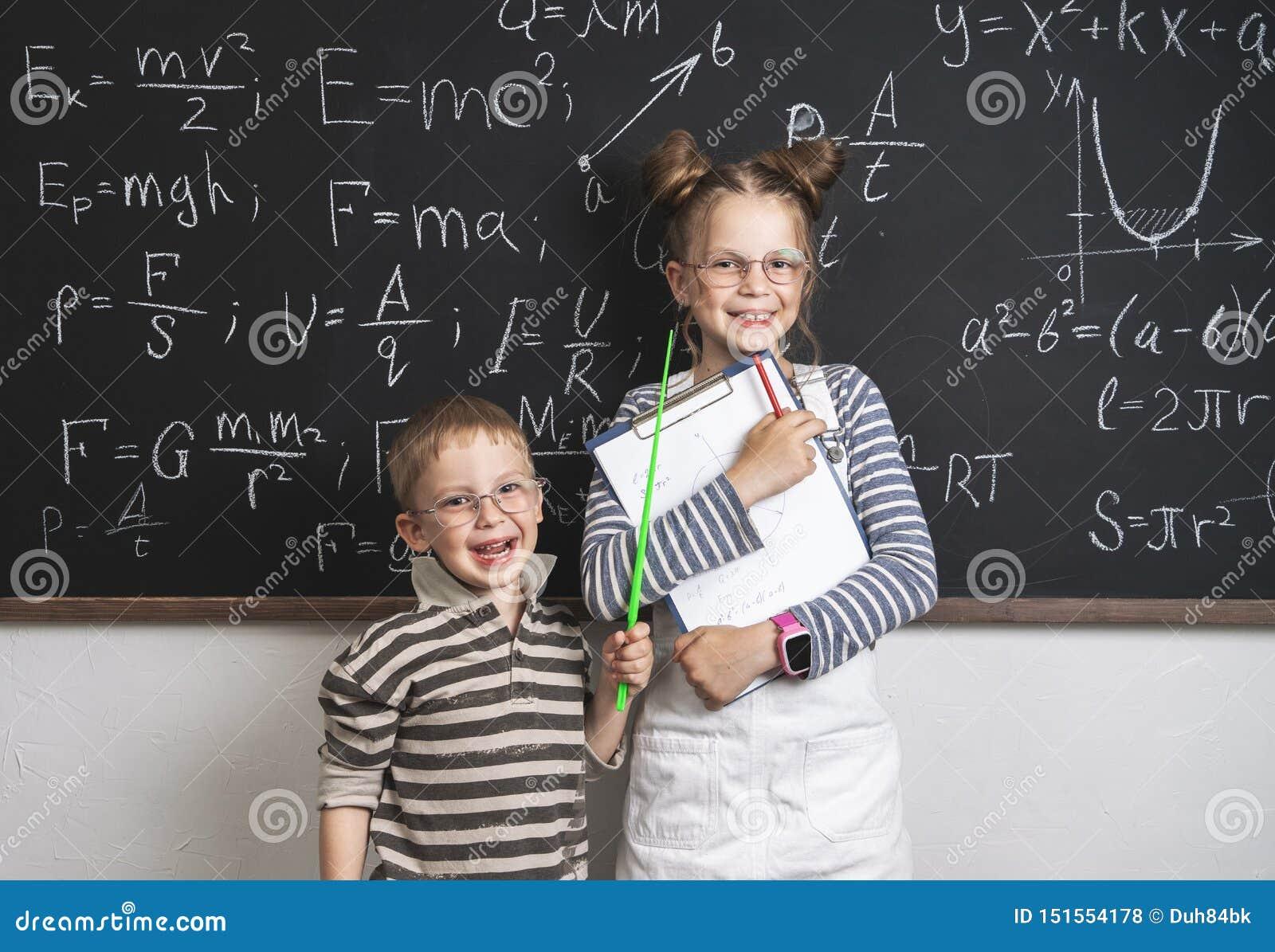 Os alunos alegres do menino e da menina estão estando no quadro-negro e nos stetrads Muitas fórmulas são escritas no quadro-negro