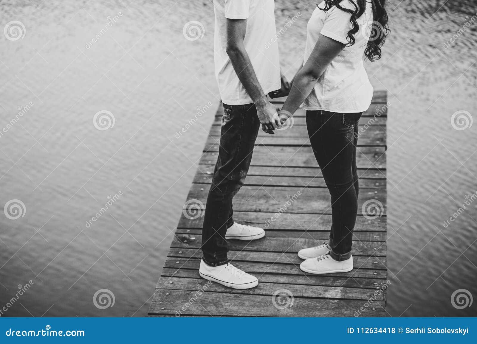 Os amantes novos emparelham-se, guardado das mãos em uma ponte de madeira perto do lago r