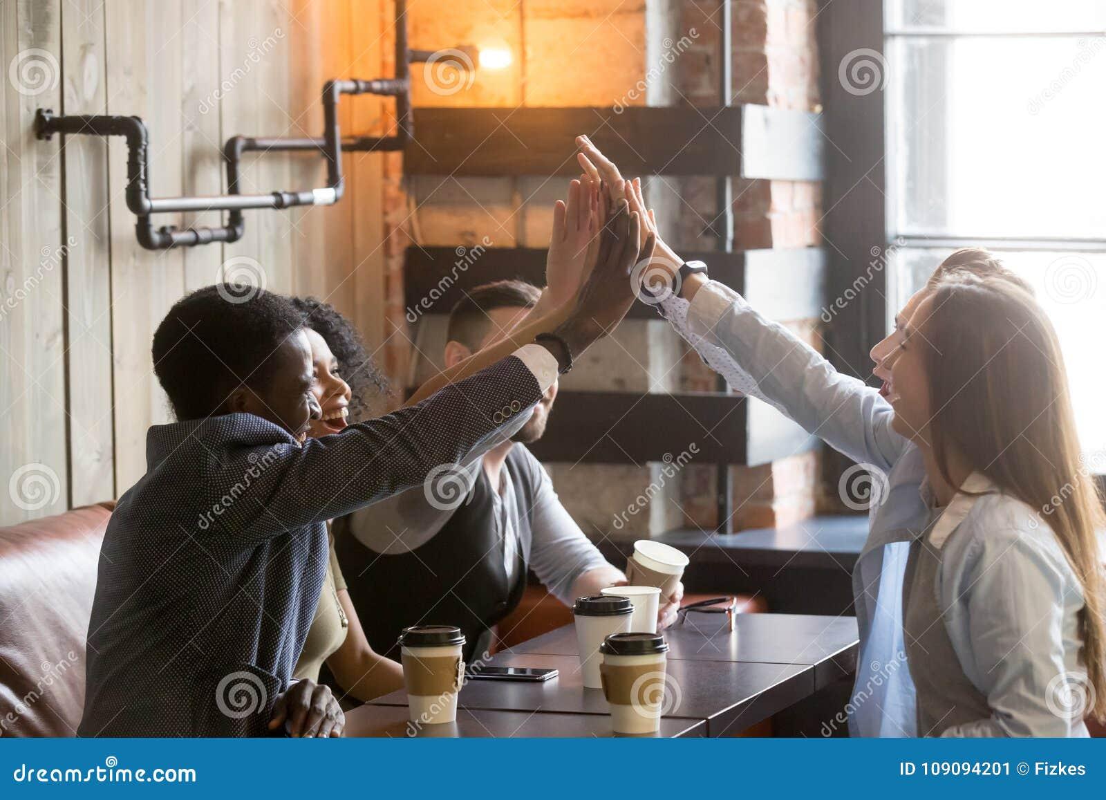Os amigos diversos juntam-se à doação das mãos junto alta-cinco no mee do café