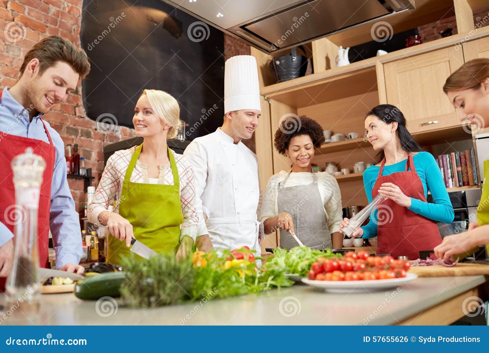 Os amigos e o cozinheiro chefe felizes cozinham o cozimento na cozinha