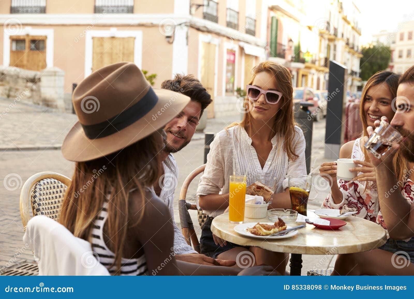 Os amigos em férias sentam a fala fora de um café em Ibiza