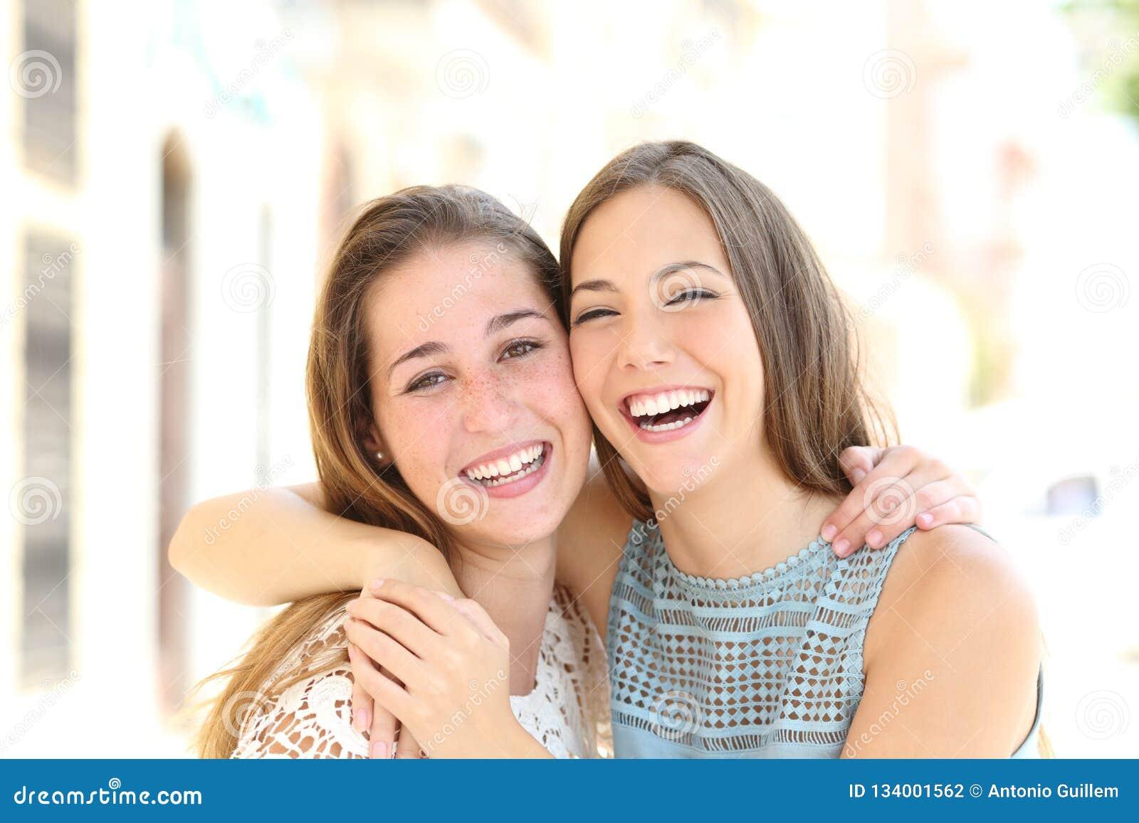 Os amigos felizes com sorriso perfeito olham-no