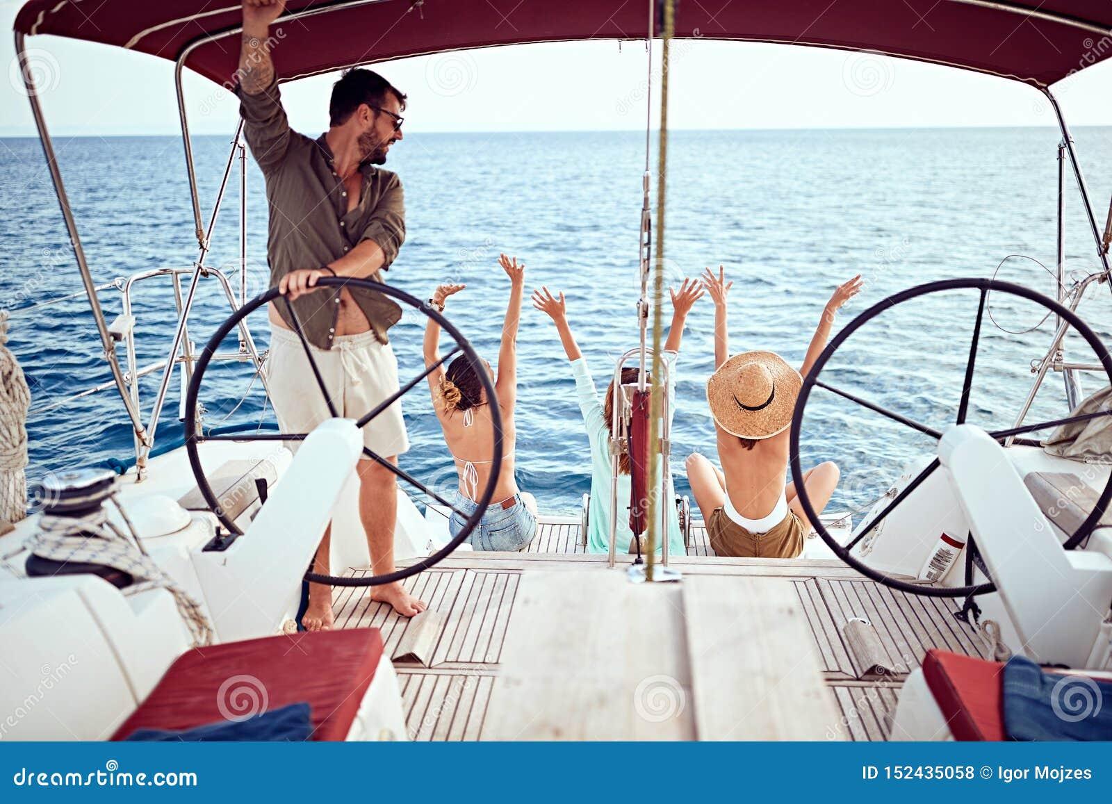 Os amigos felizes no barco apreciam junto em férias