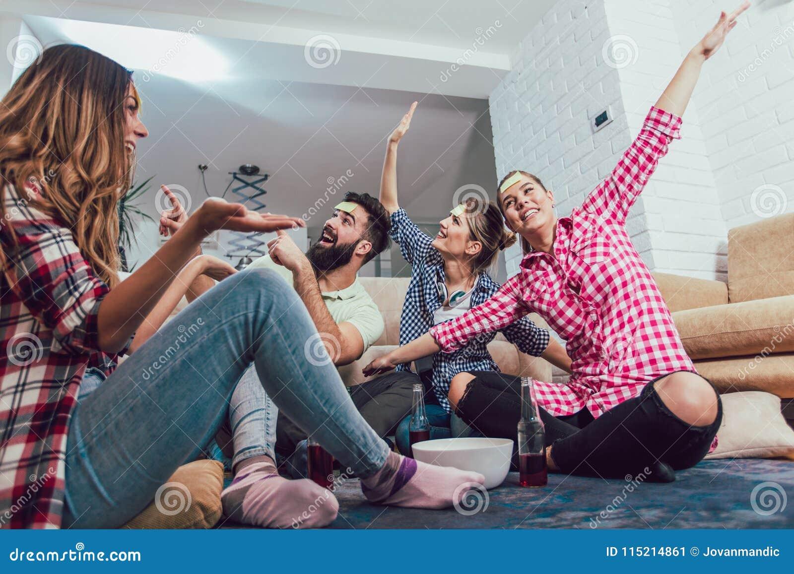 Os amigos felizes que jogam o jogo supõem quem e tendo o divertimento