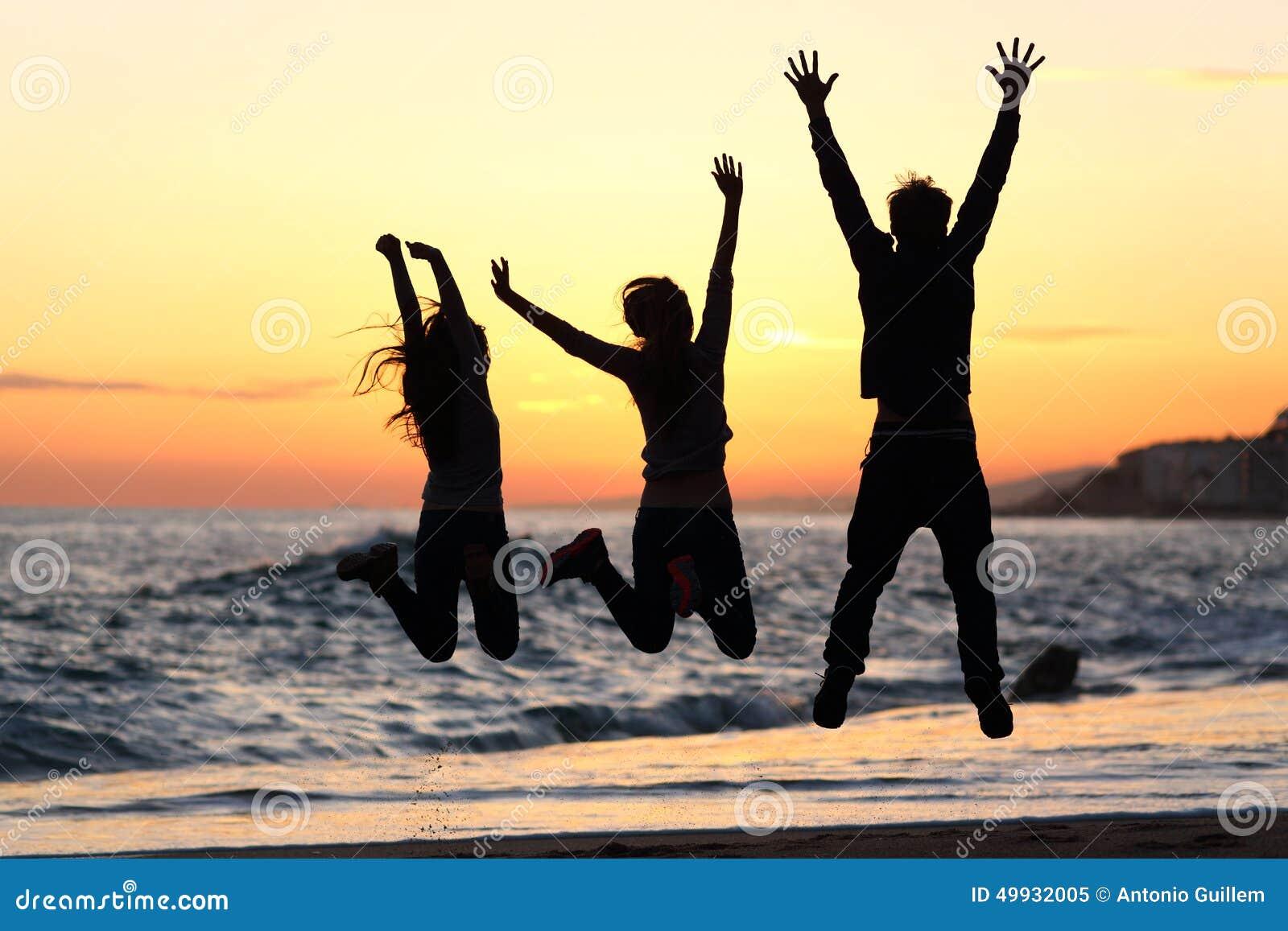 Os amigos mostram em silhueta o salto feliz na praia no por do sol