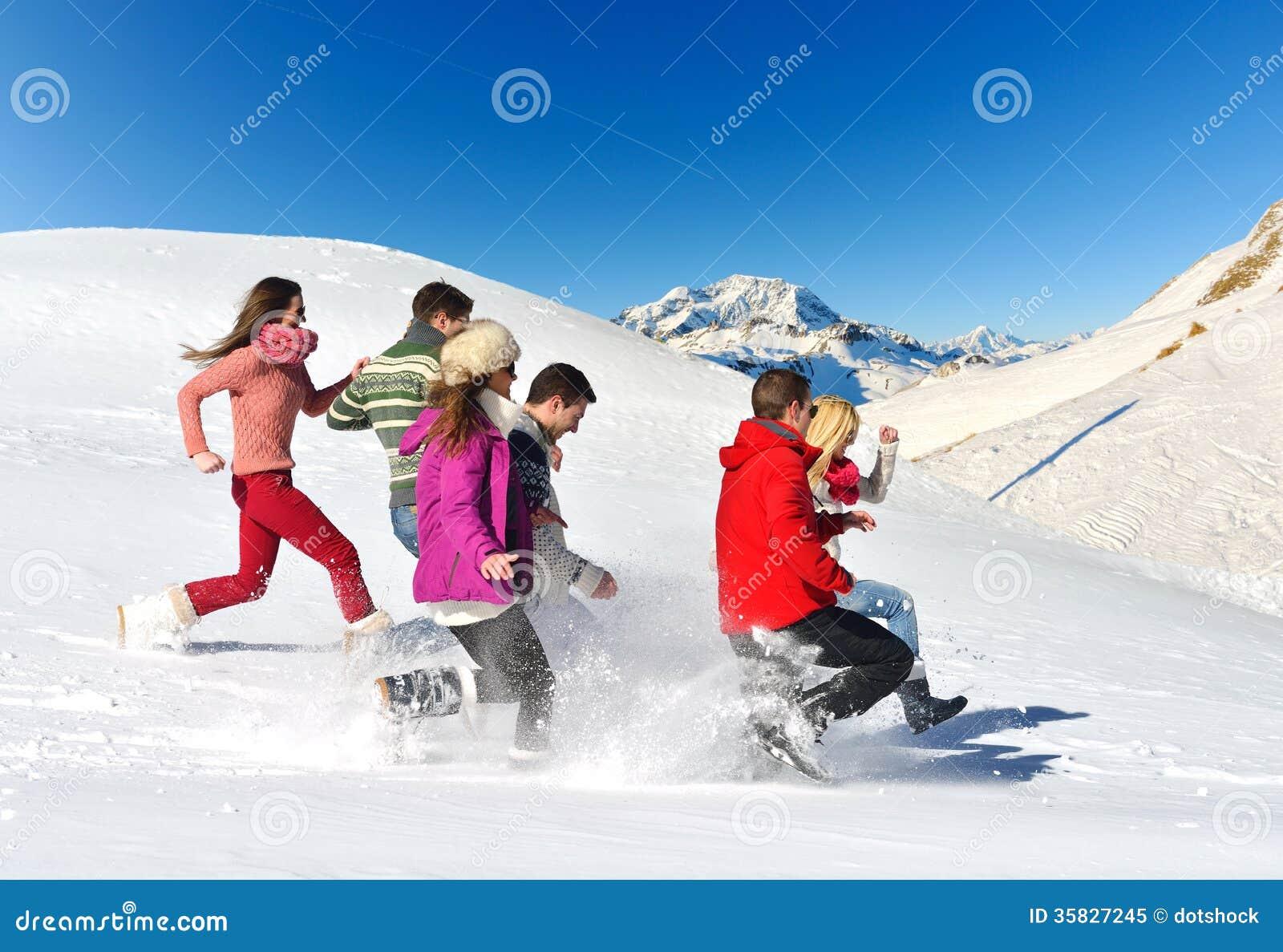 Os amigos têm o divertimento no inverno na neve fresca