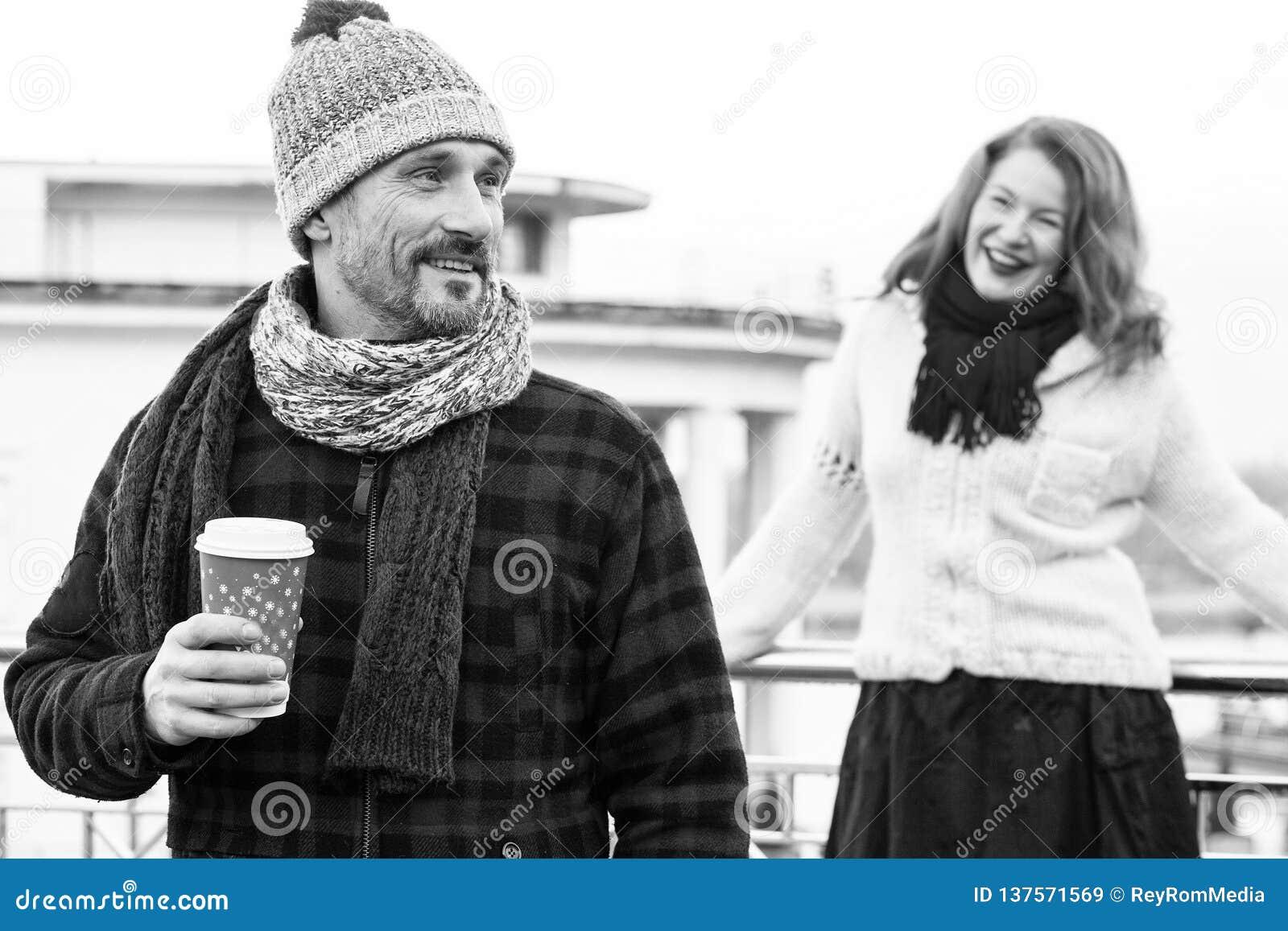 Os amores felizes dos pares bebem o café exterior O indivíduo de sorriso guarda o copo do ofício com café e escondê-lo da amiga a