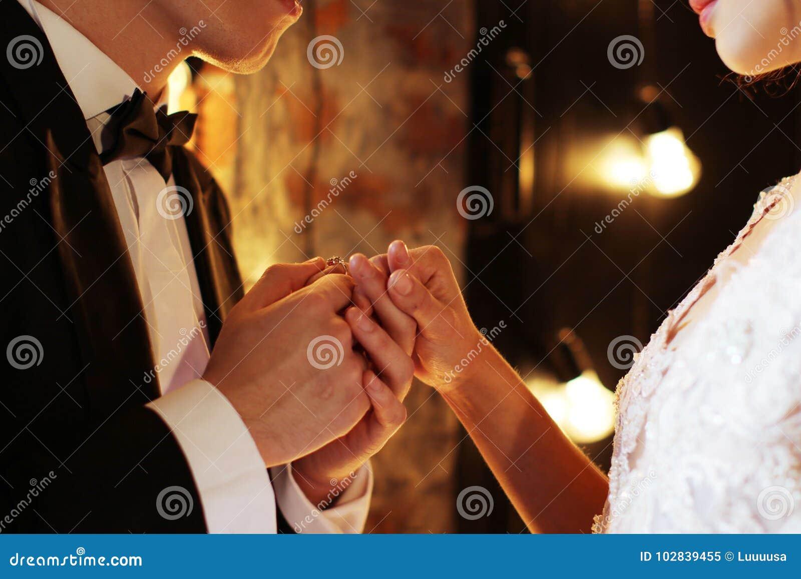 Os anéis da troca dos recém-casados, noivo põem o anel sobre a mão do ` s da noiva no escritório de registro da união Fundo de Br