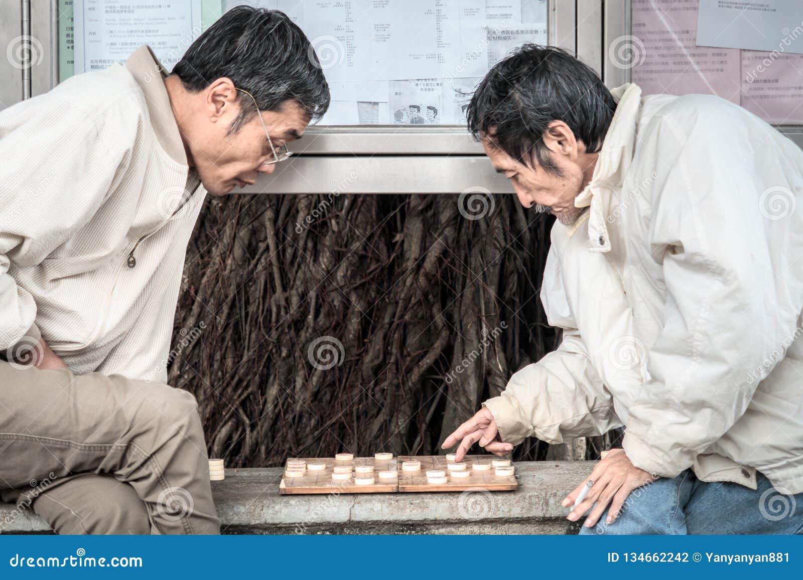 Os anciões chineses aposentados jogam a xadrez chinesa na rua de Hong Kong