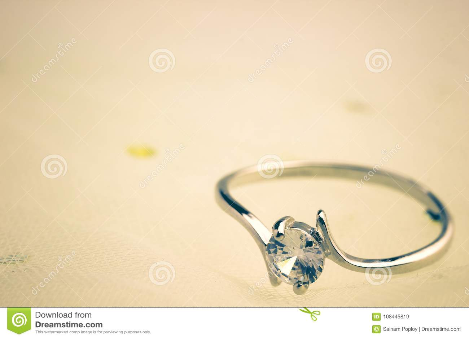 Os aneis de diamante falsificados são colocados em um vestido de casamento branco