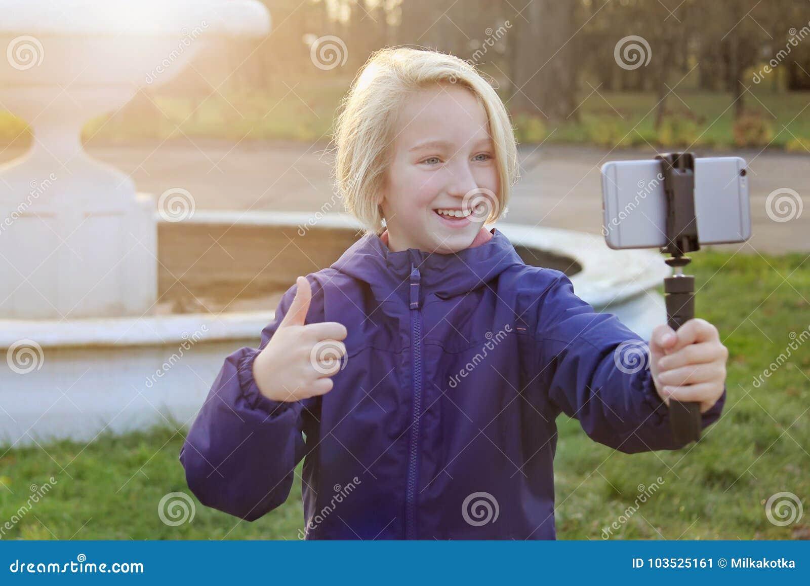 Os anos de idade bonitos de sorriso da menina 9-11 do preteen que tomam um selfie fora Criança que toma um autorretrato com telef