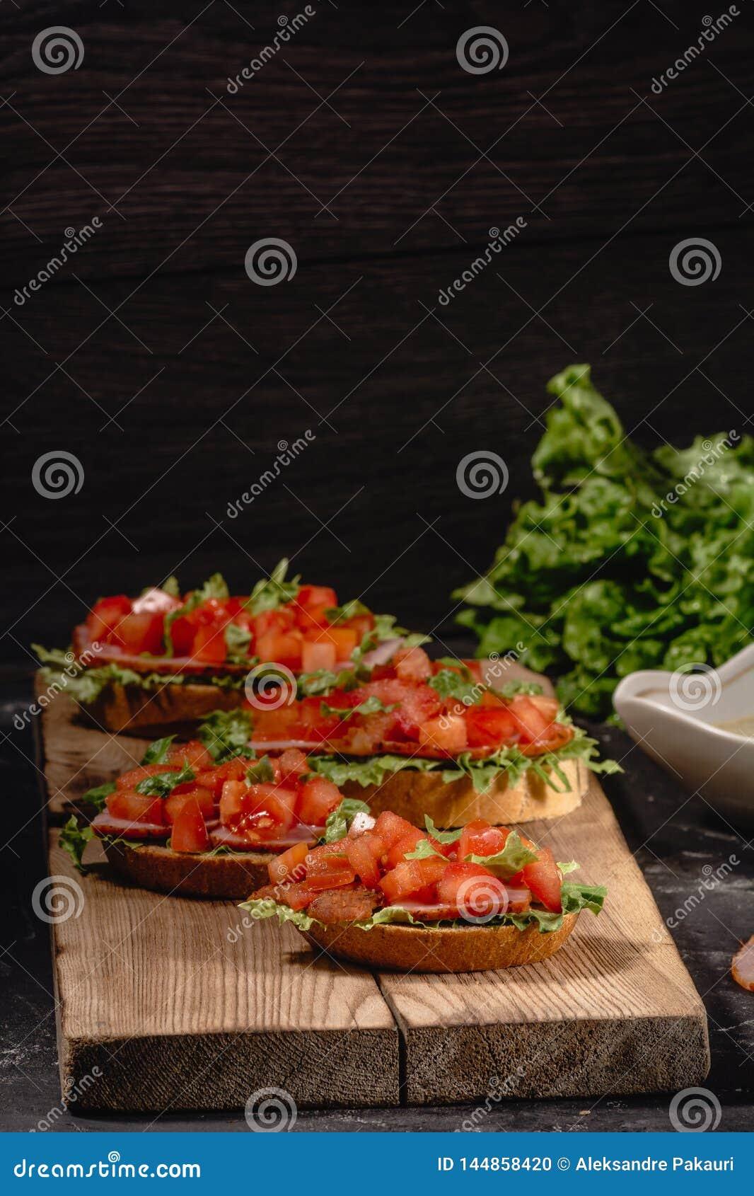 Os aperitivos italianos do tomate saboroso saboroso, ou o bruschetta, em fatias de baguette brindado decorado com folhas da salad