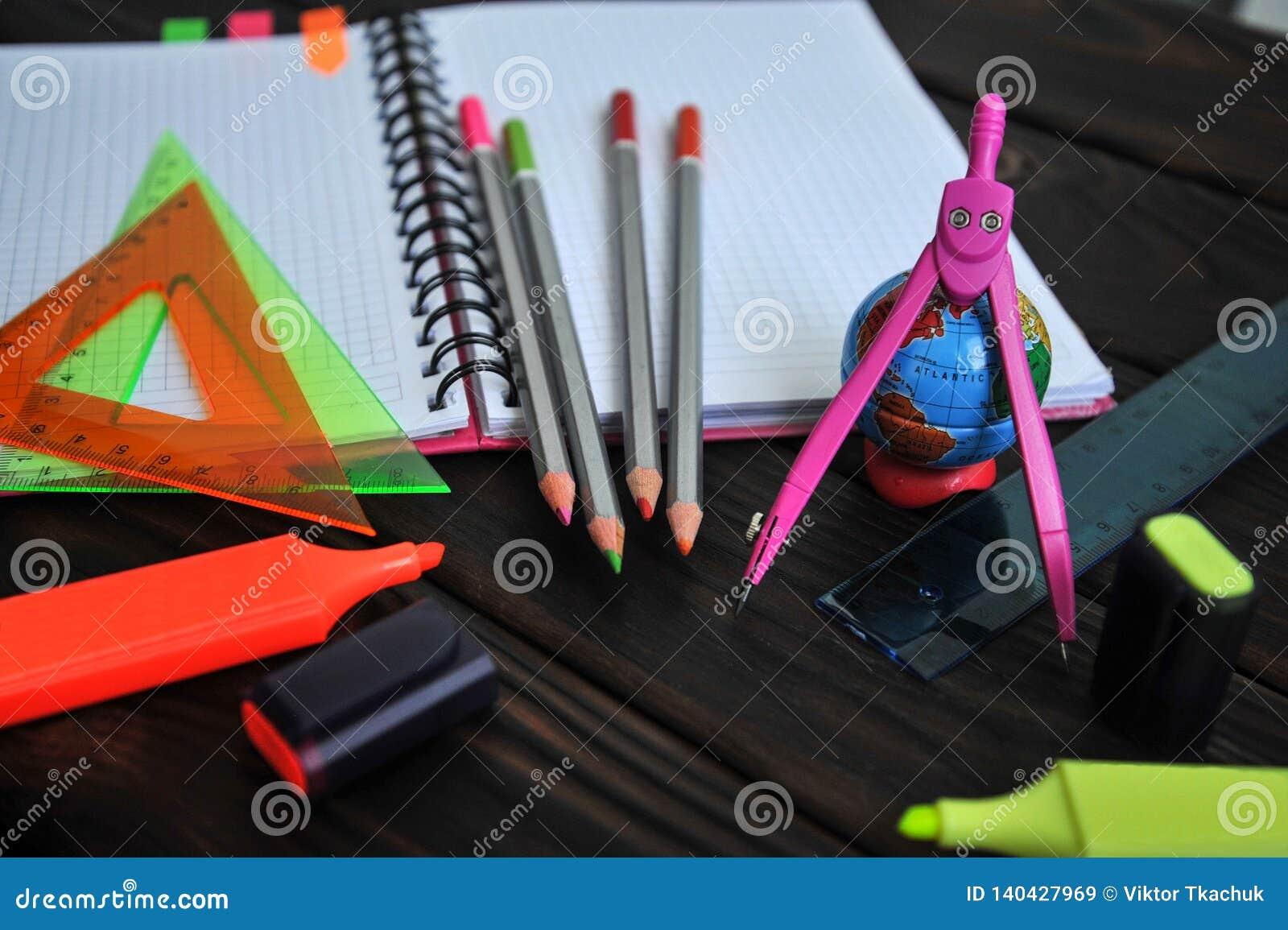 Os artigos de papelaria com um globo espalharam para fora em um caderno que encontra-se em uma tabela de madeira escura
