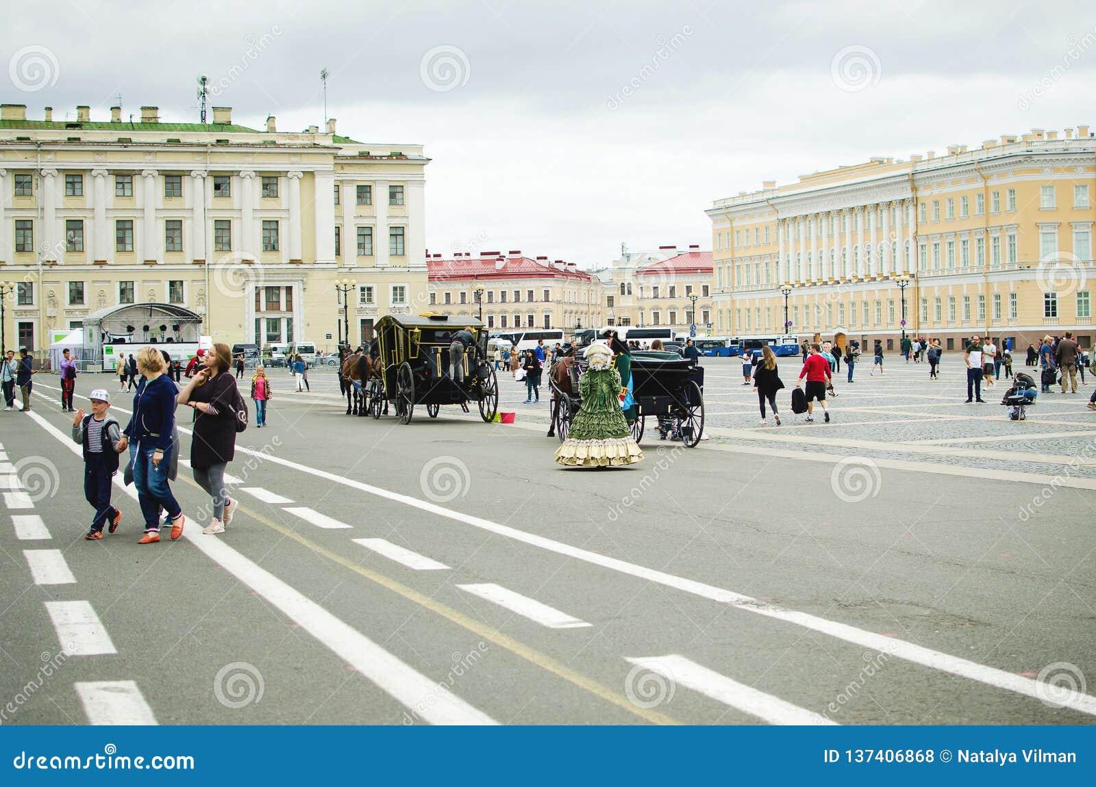 Os artistas em trajes antigos mantem distraído turistas no quadrado do palácio em St Petersburg