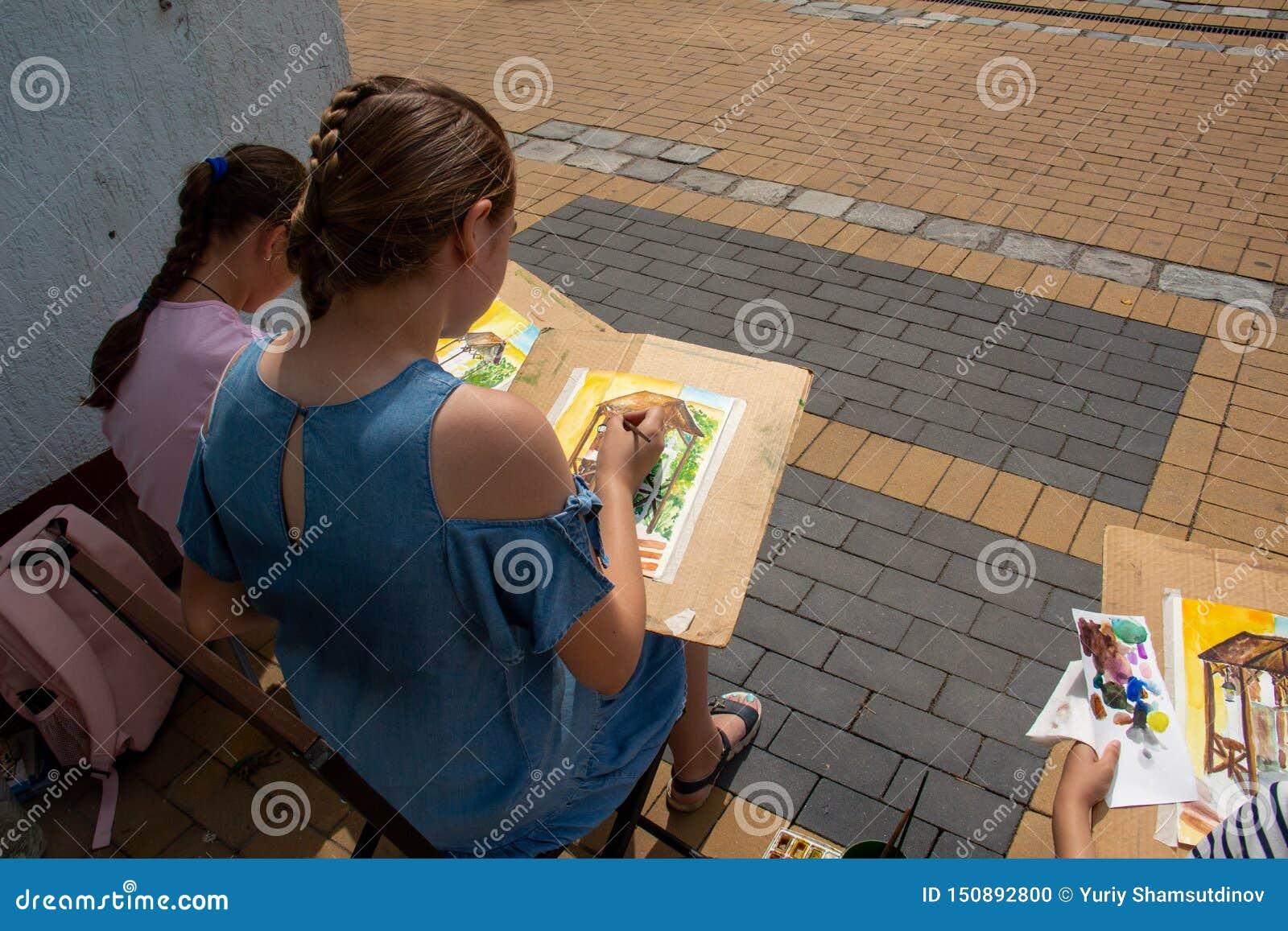 Os artistas novos da rua aprendem pintar construções