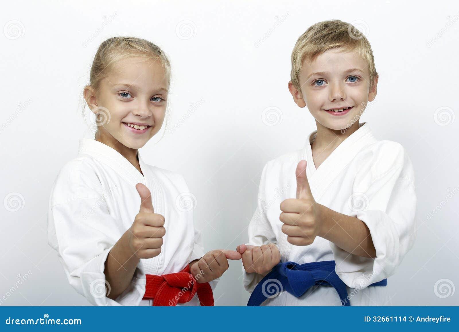 Os atletas das crianças com correias mostram os polegares acima
