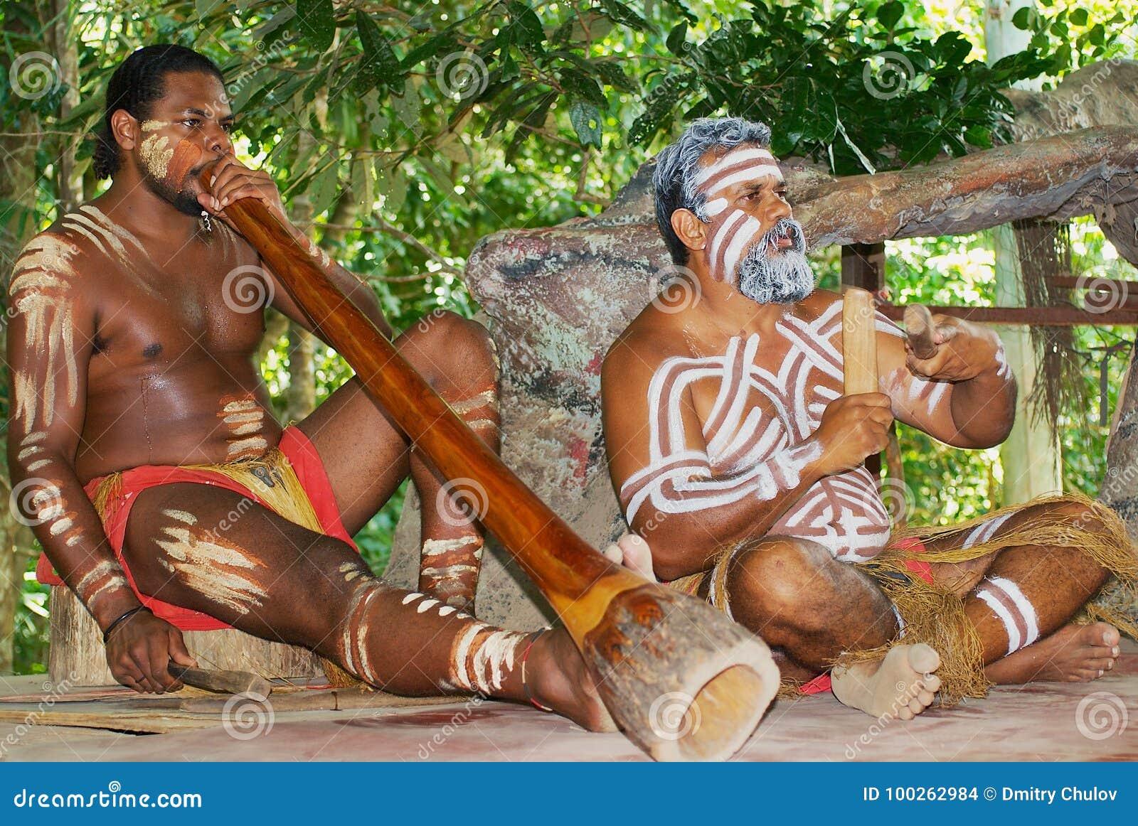 Os atores do aborígene executam a música com os instrumentos tradicionais no parque da cultura de Tjapukai em Kuranda, Queensland
