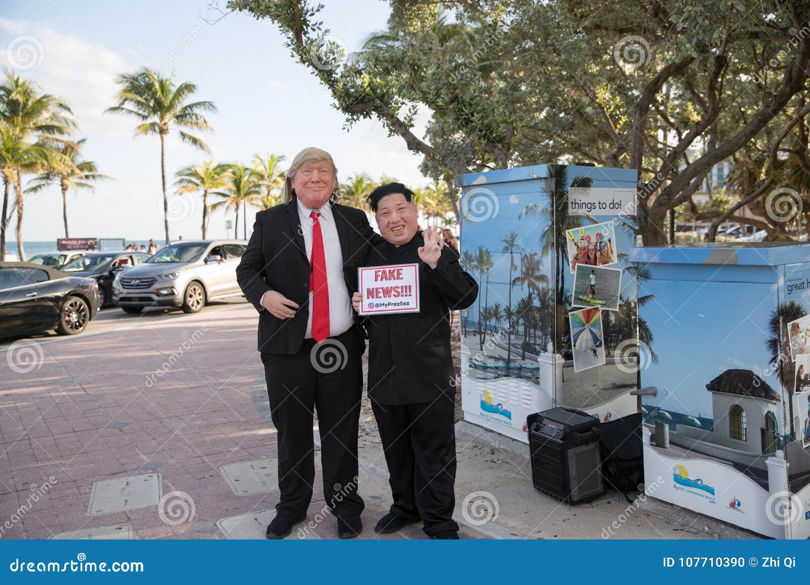 Os atores que jogam o trunfo e o Kim Jong-Un guardam o cartaz falsificado do ` da notícia do ` Praia de Fort Lauderdale