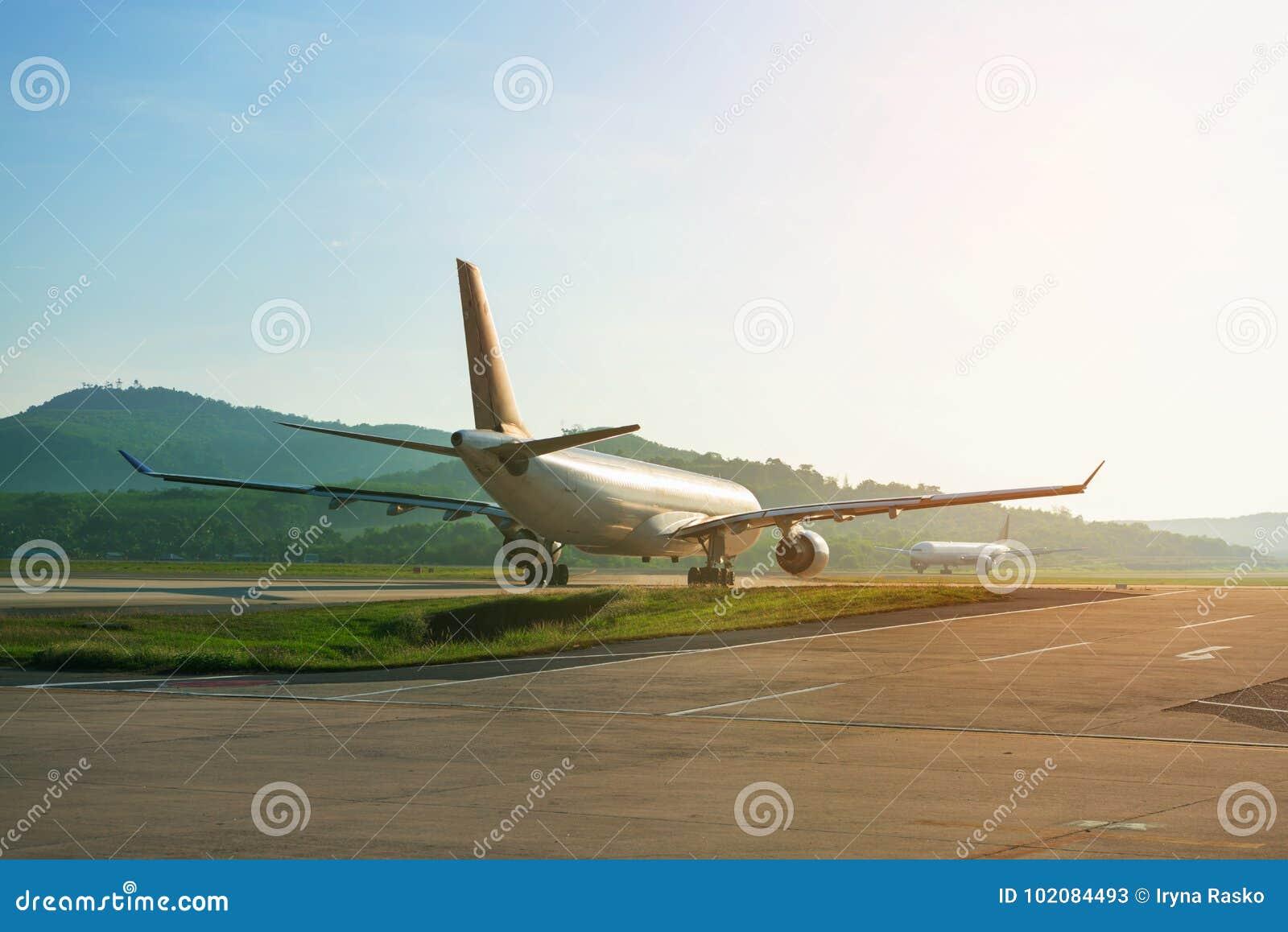 Os aviões grandes do passageiro na tira da pista de decolagem taxiing para a decolagem