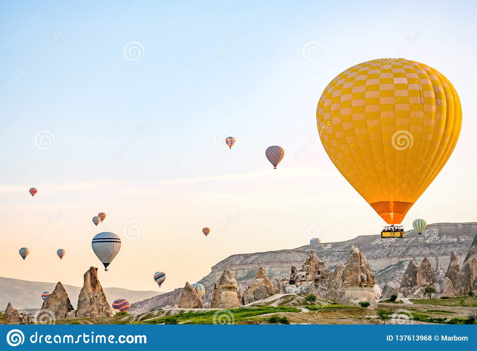 Os balões de ar quente coloridos que voam sobre a rocha ajardinam em Cappadocia Turquia