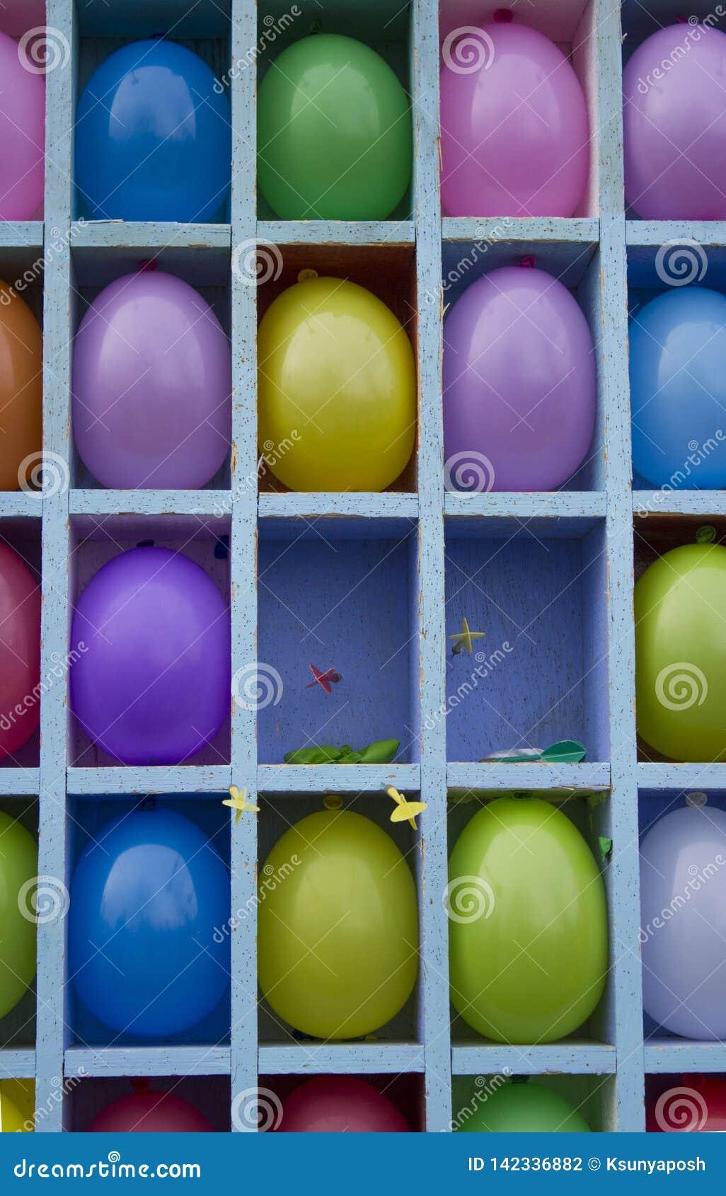 Os balões infláveis amarelos, vermelhos, roxos, azuis são divididos nos setores projetados jogar dardos