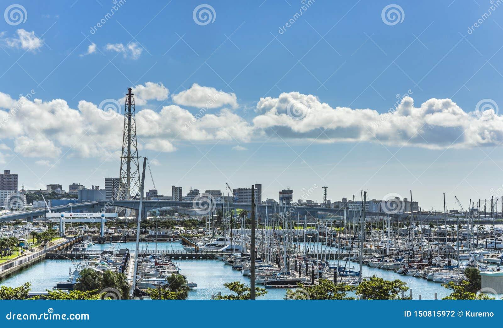 Os barcos do lazer alinharam no porto do porto de Ginowan visto do centro de conversão de Okinawa
