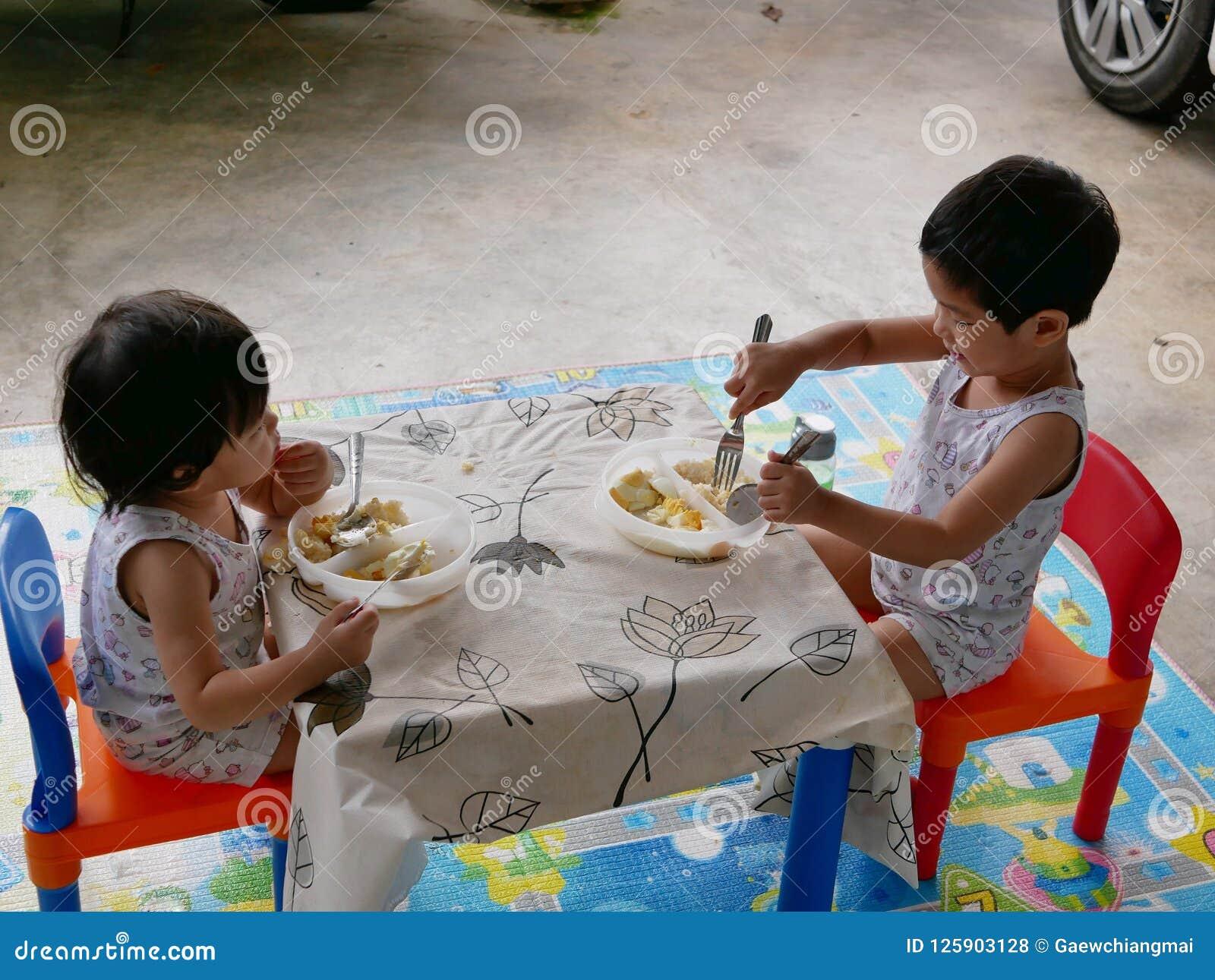 Os bebês asiáticos pequenos apreciam comer o alimento sós