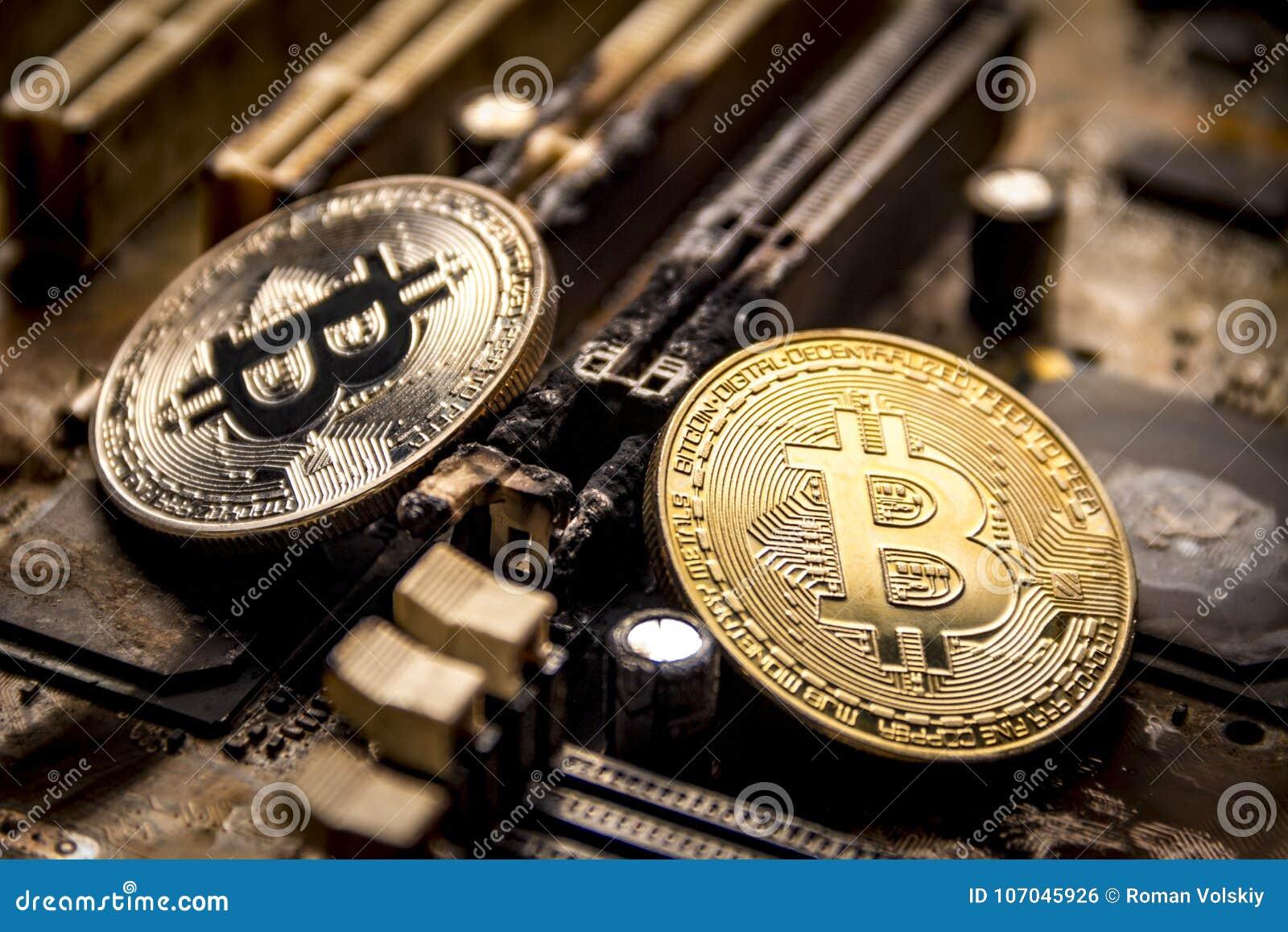 Os bitcoins do ouro e da prata no fundo de um computador eletrônico queimado embarcam