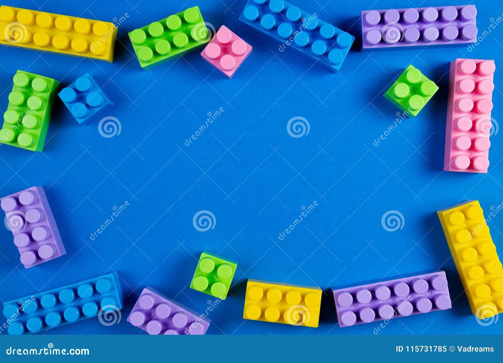 Os blocos plásticos coloridos da construção no fundo azul como crianças brincam o quadro