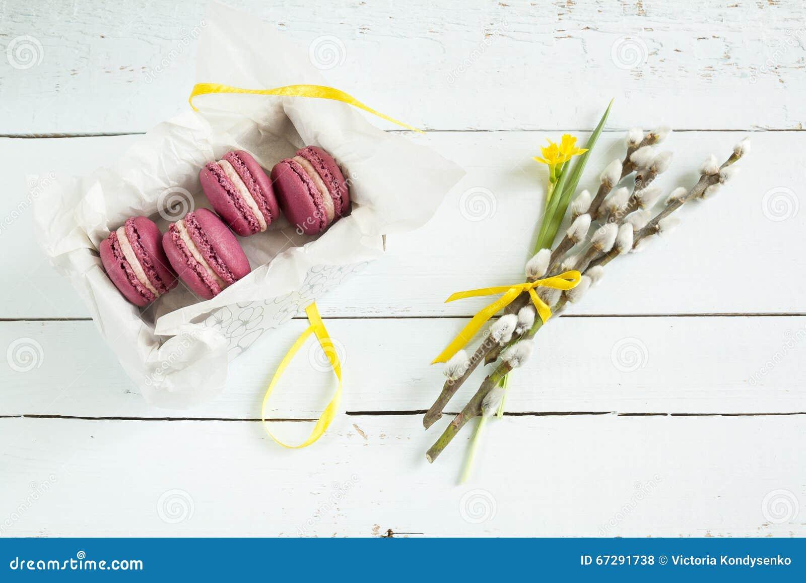 Os bolinhos de amêndoa franceses carmesins doces com o salgueiro da caixa, do narciso amarelo (narciso) e de bichano na luz tingi