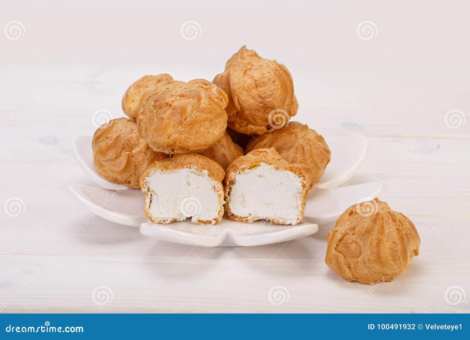 Os bolos frescos dos sopros de creme de Profiteroles encheram-se com o creme de pastelaria dentro