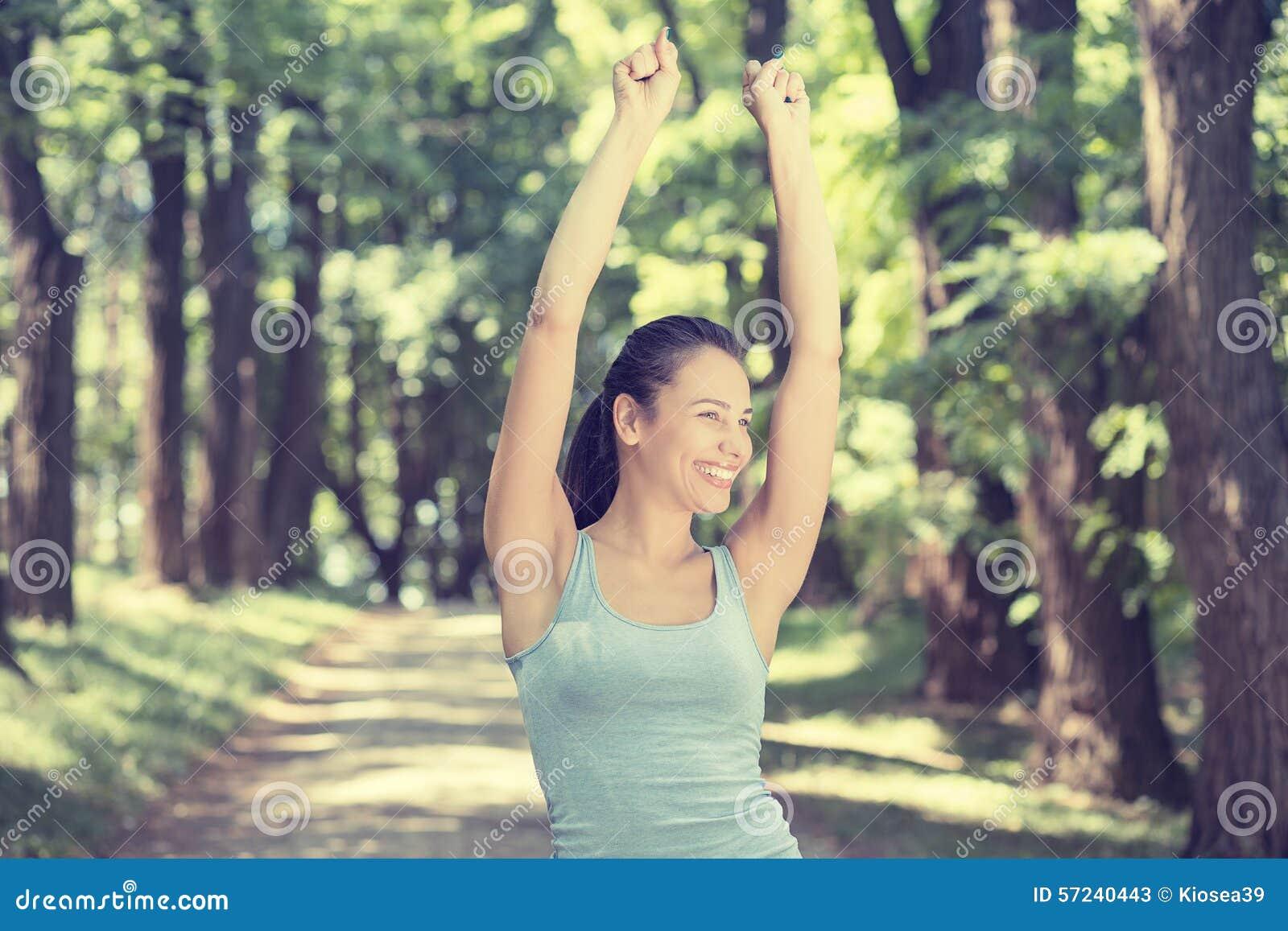 Os braços aptos da mulher aumentaram até o céu que comemora a liberdade