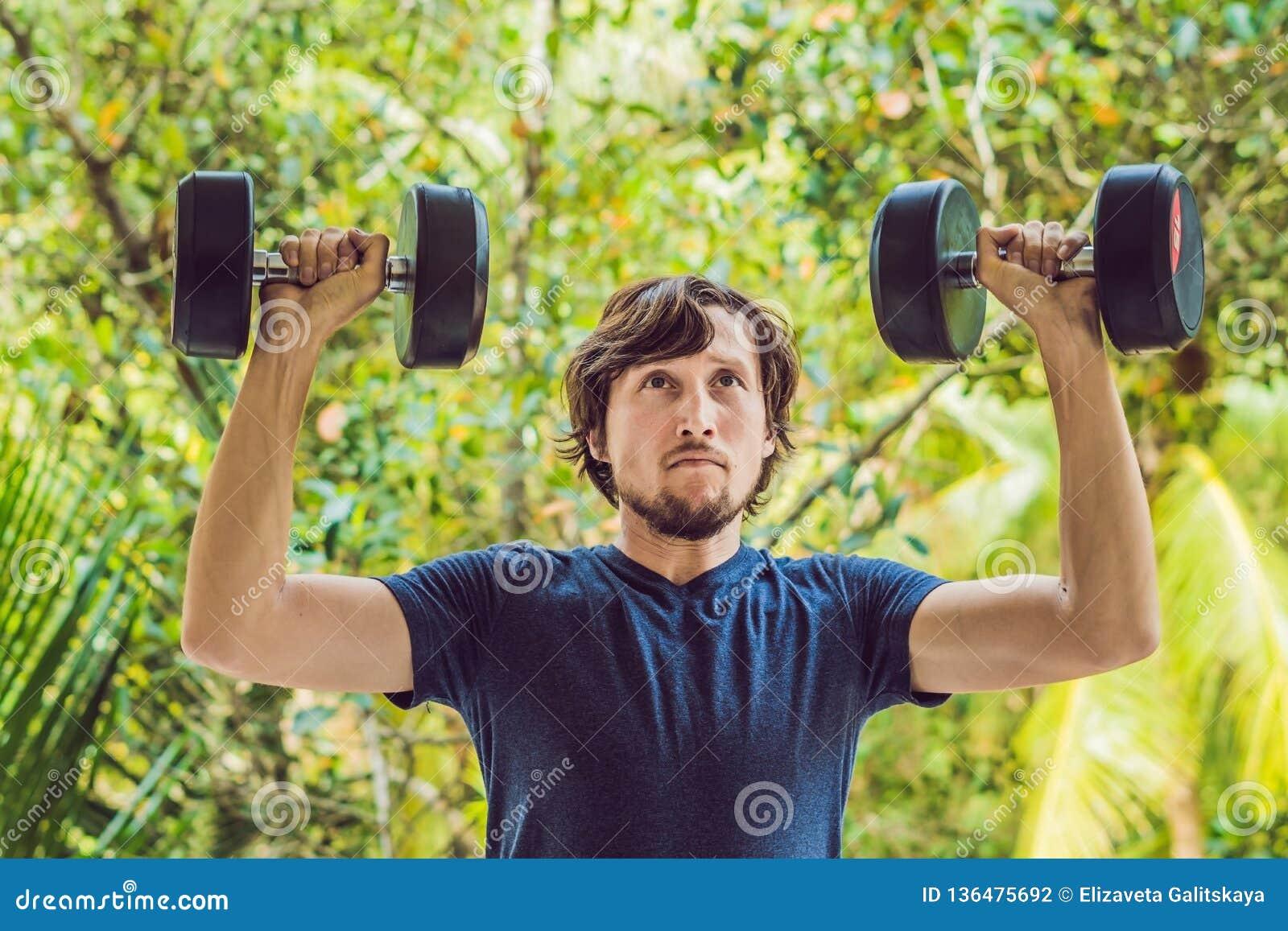 Os braços dando certo exteriores do homem da aptidão do treinamento que levantam os pesos que fazem os bíceps ondulam O homem ost