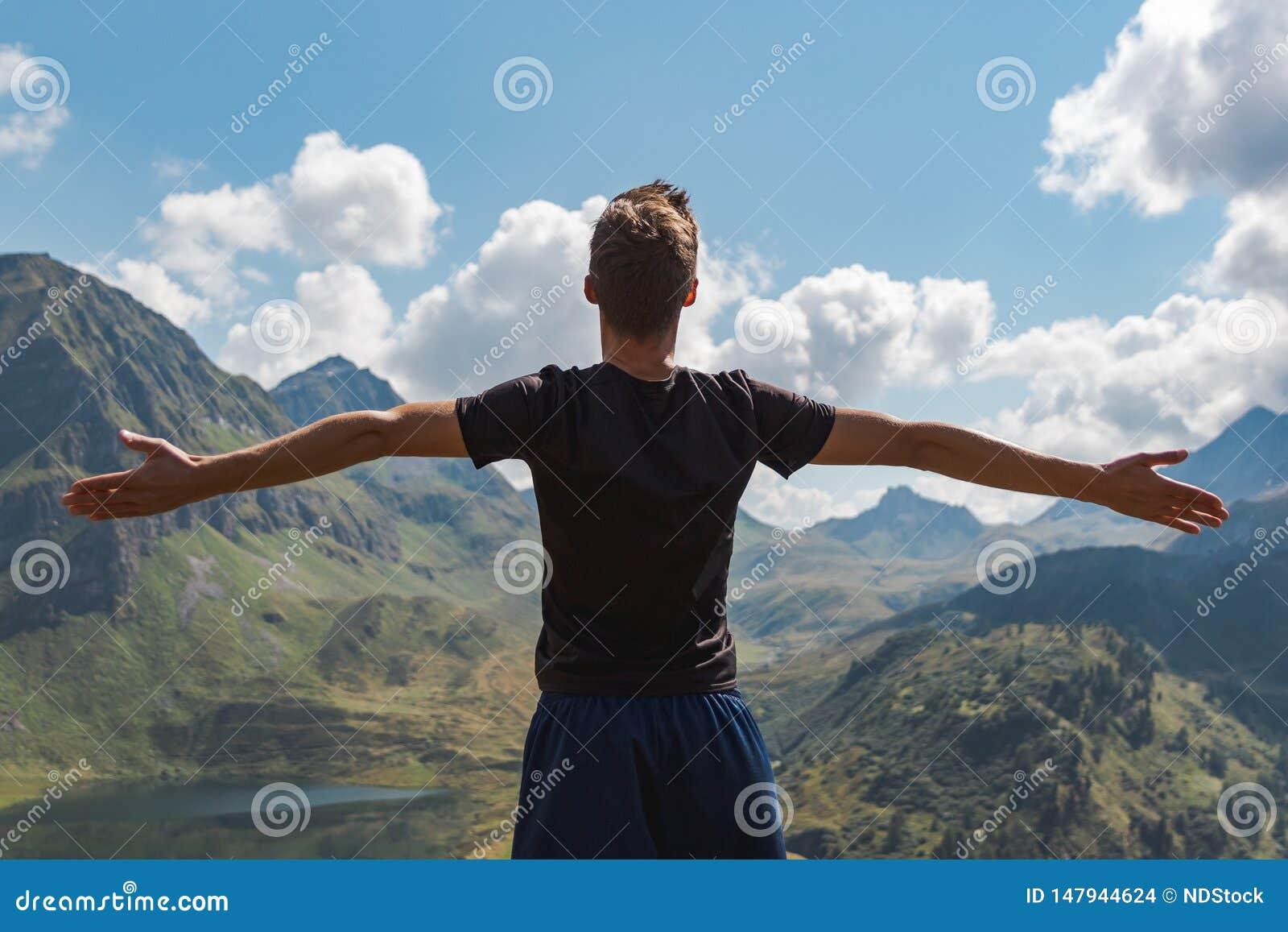 Os braços de homem de jovens levantaram a apreciação da liberdade nas montanhas durante um dia ensolarado