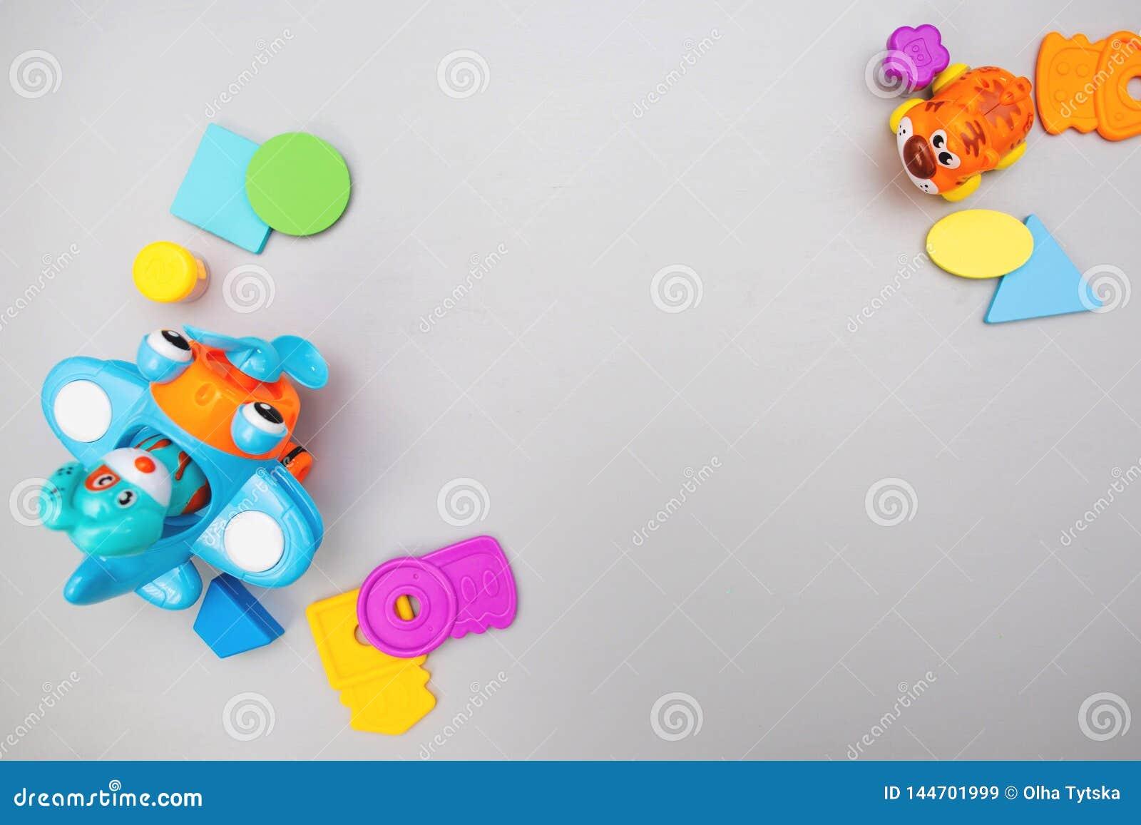 Os brinquedos coloridos das crian?as em um fundo cinzento com espa?o para o texto Configura??o lisa, vista superior