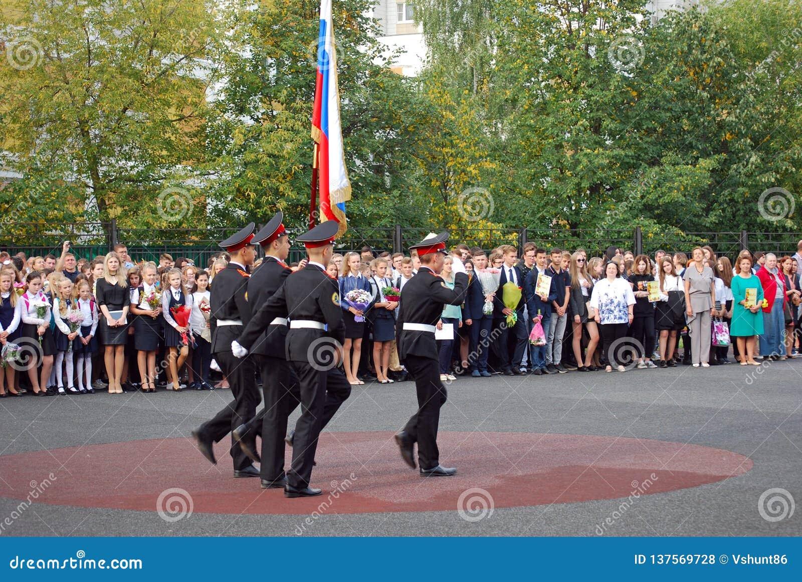 Os cadete marcham com uma bandeira em uma régua da manhã antes da escola na parada-terra Estudantes da escola