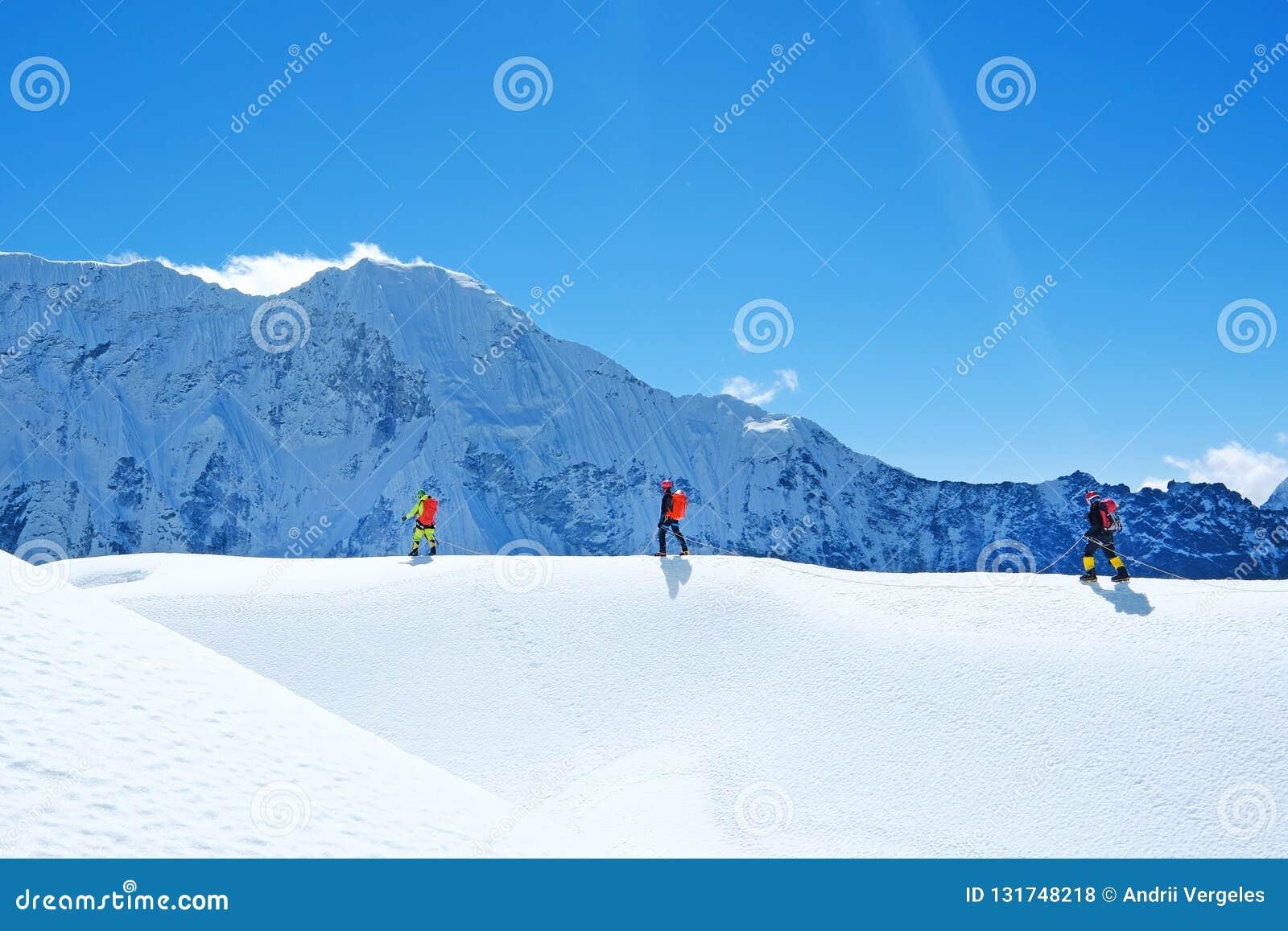 Os caminhantes com trouxas alcançam a cimeira do pico de montanha Liberdade do sucesso e realização da felicidade nas montanhas E